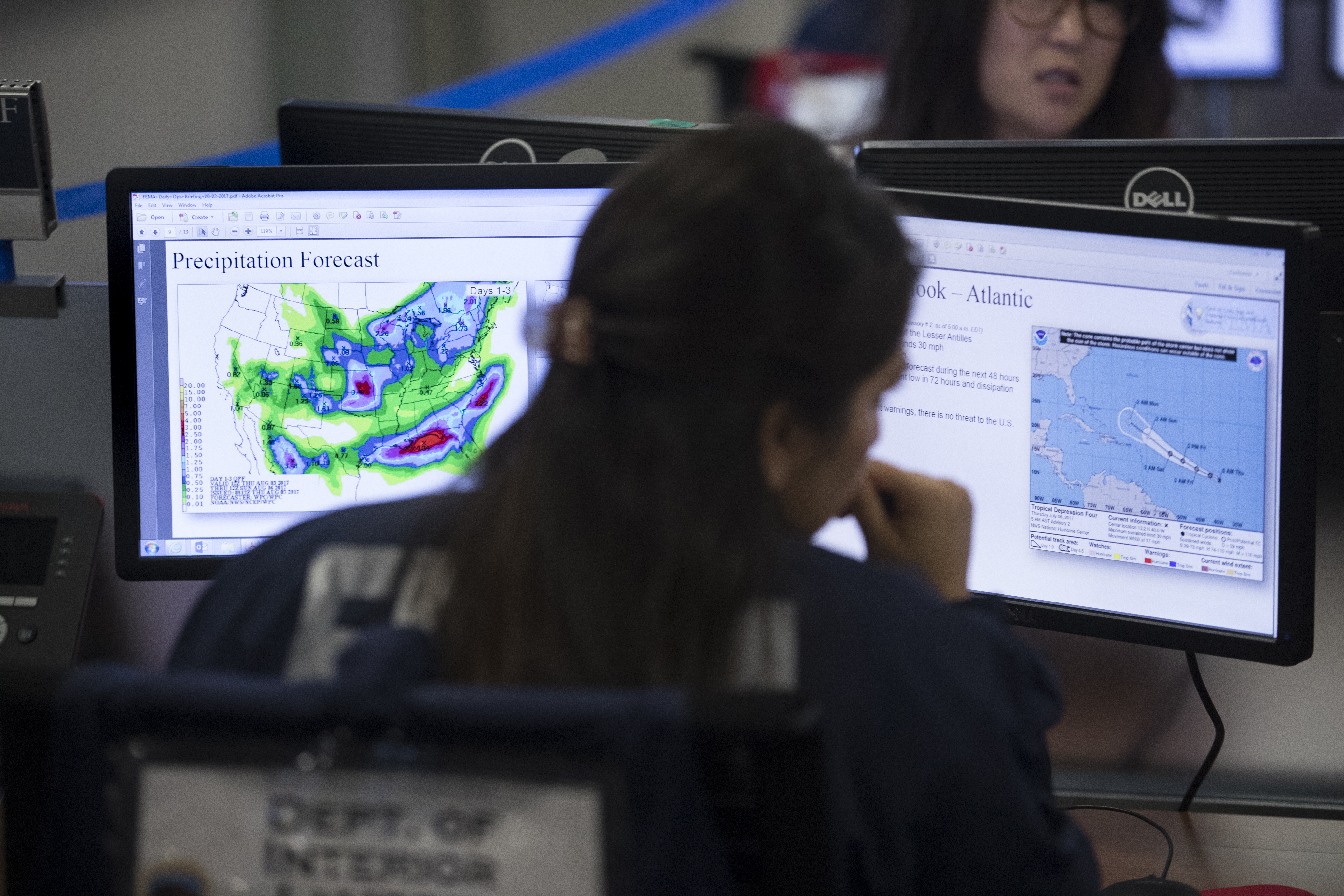 A woman at her desk looks at two computer screens showing weather data.