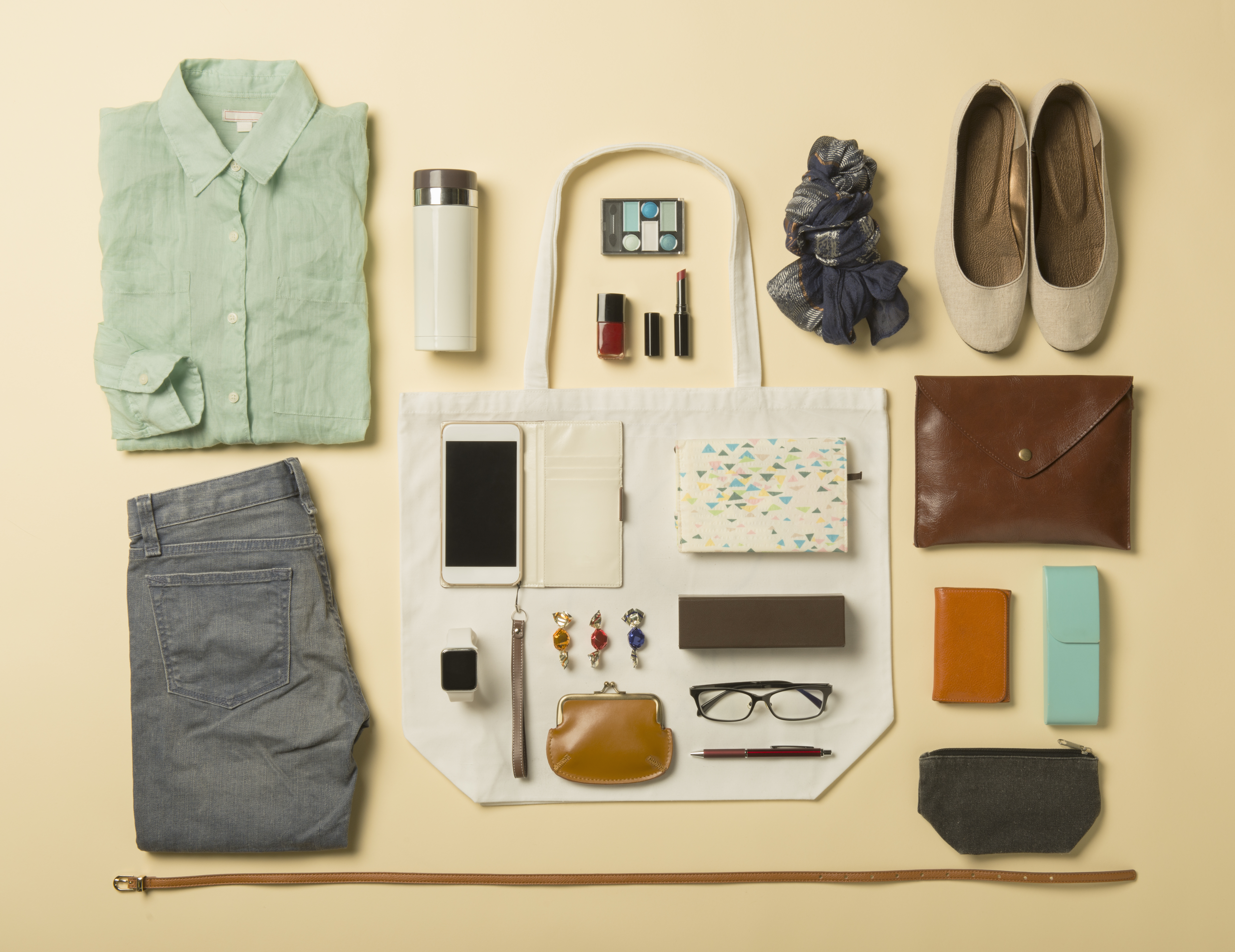 Clothes, shoes, and accessories neatly laid out on a seamless background.