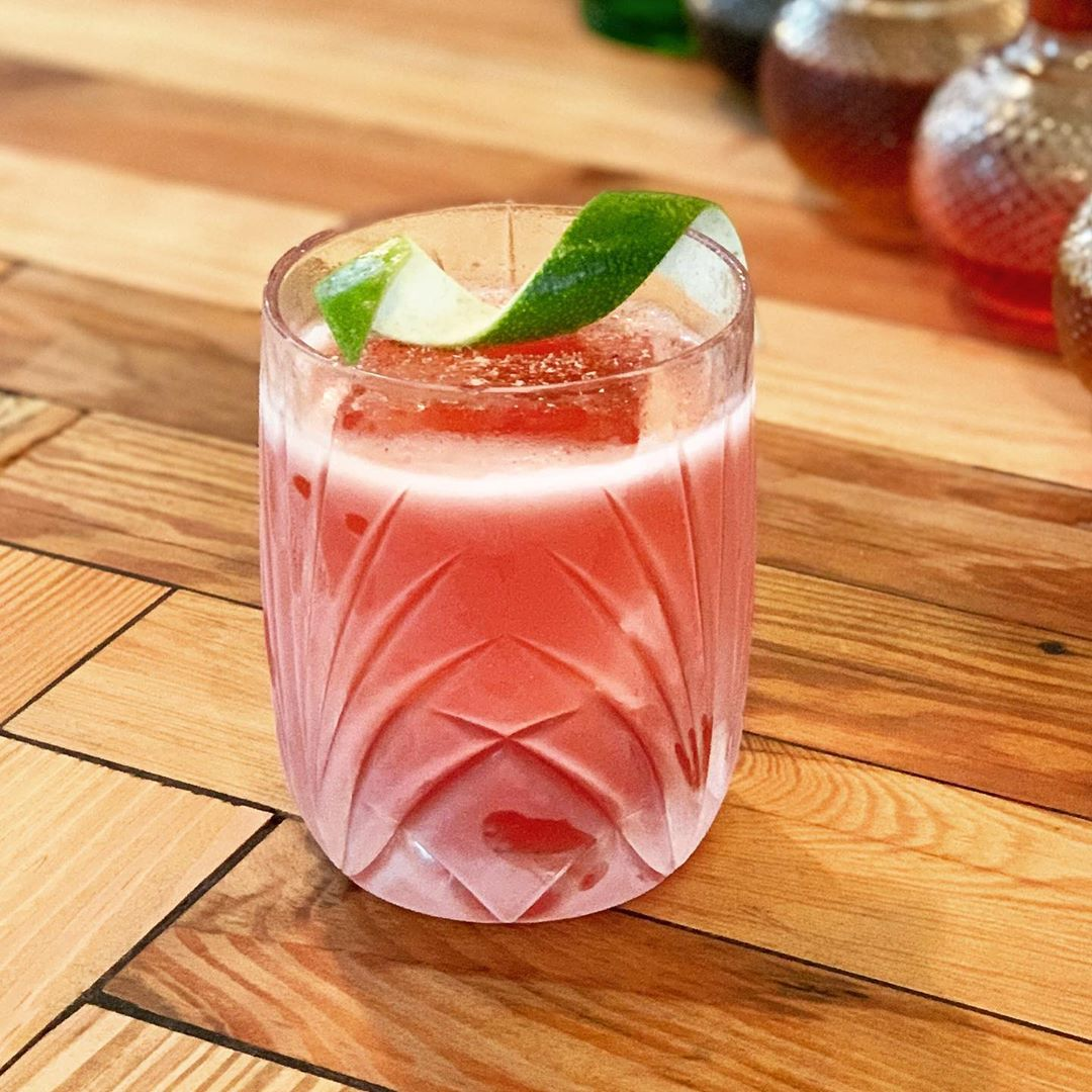 A rocks glass containing a Lion's Tail cocktail with a twist of lime