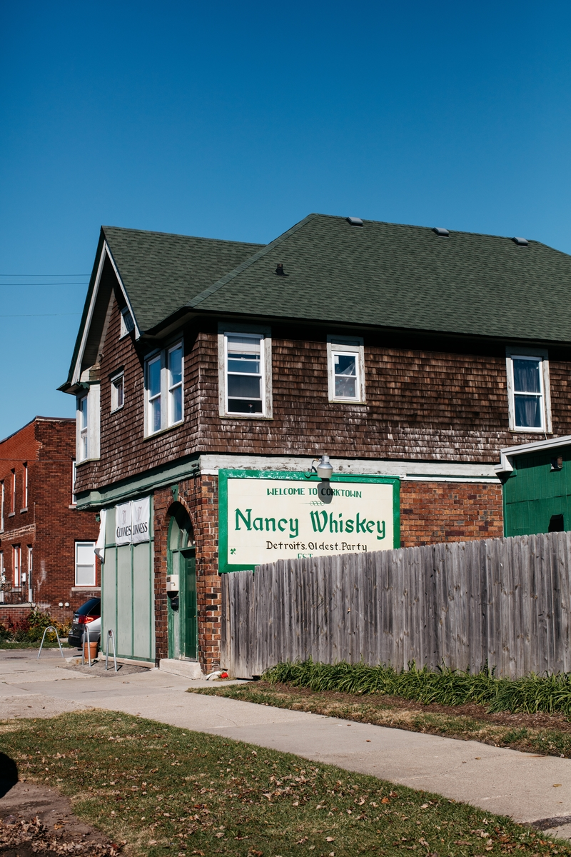 The exterior of Nancy Whiskey's is covered in wood cladding with a green roof on a sunny, cloudless day.