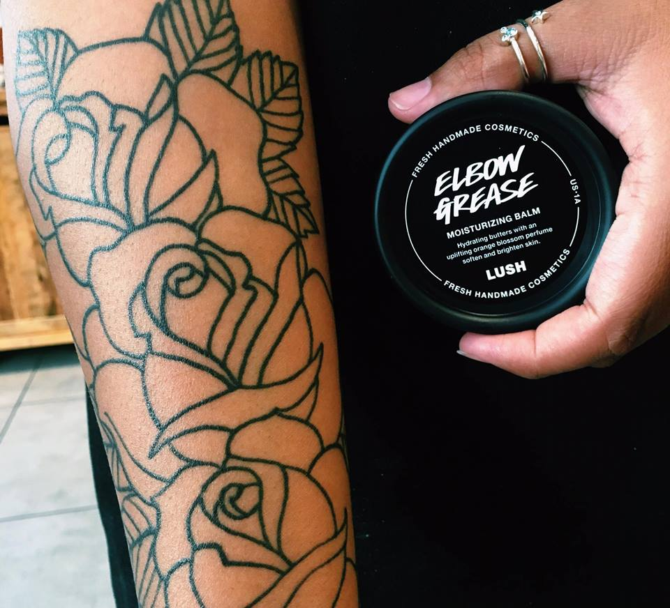 A woman with a tattoo holding a jar of Lush moisturizer
