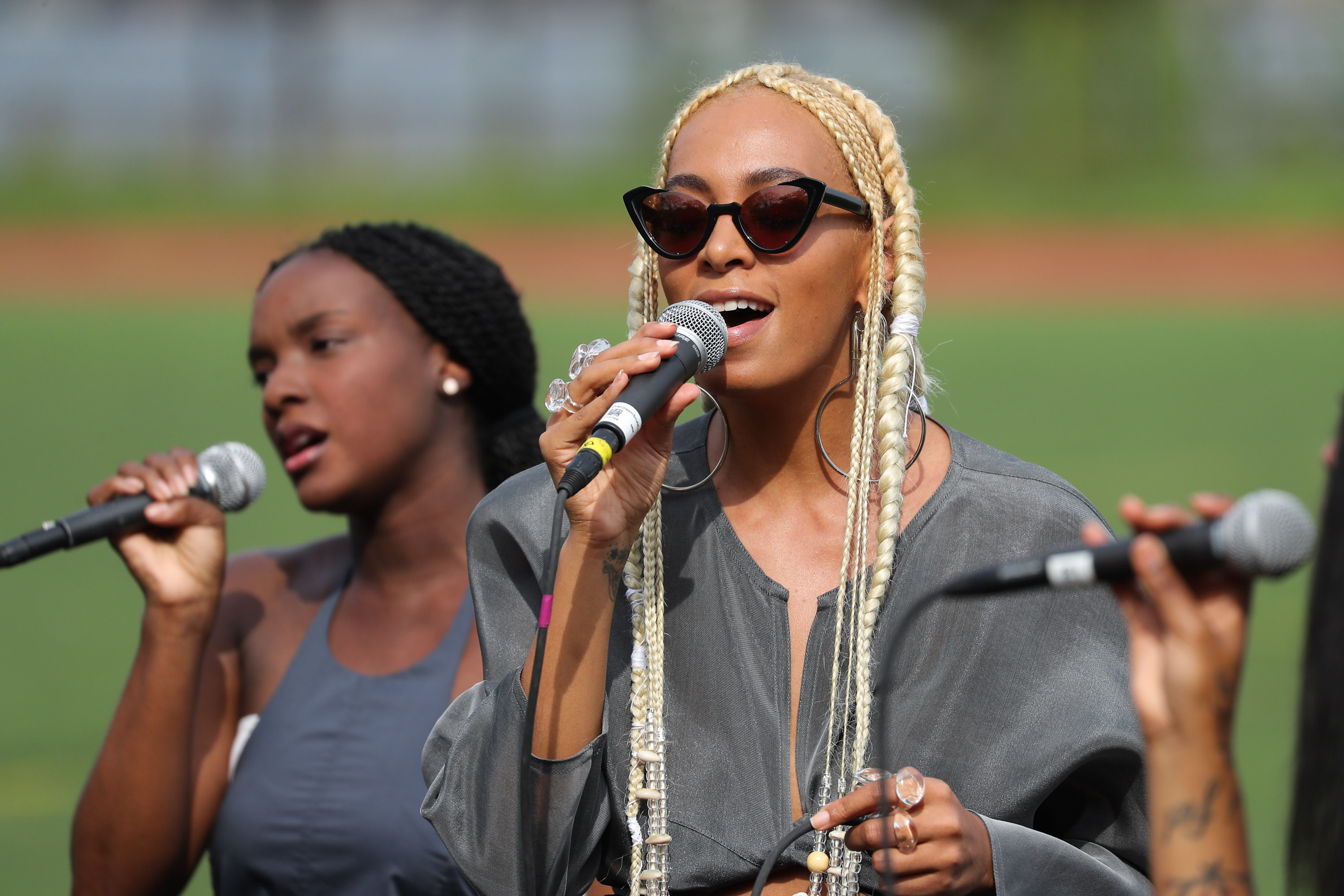 Solange is behind the mic, wearing a gray top by the designer.