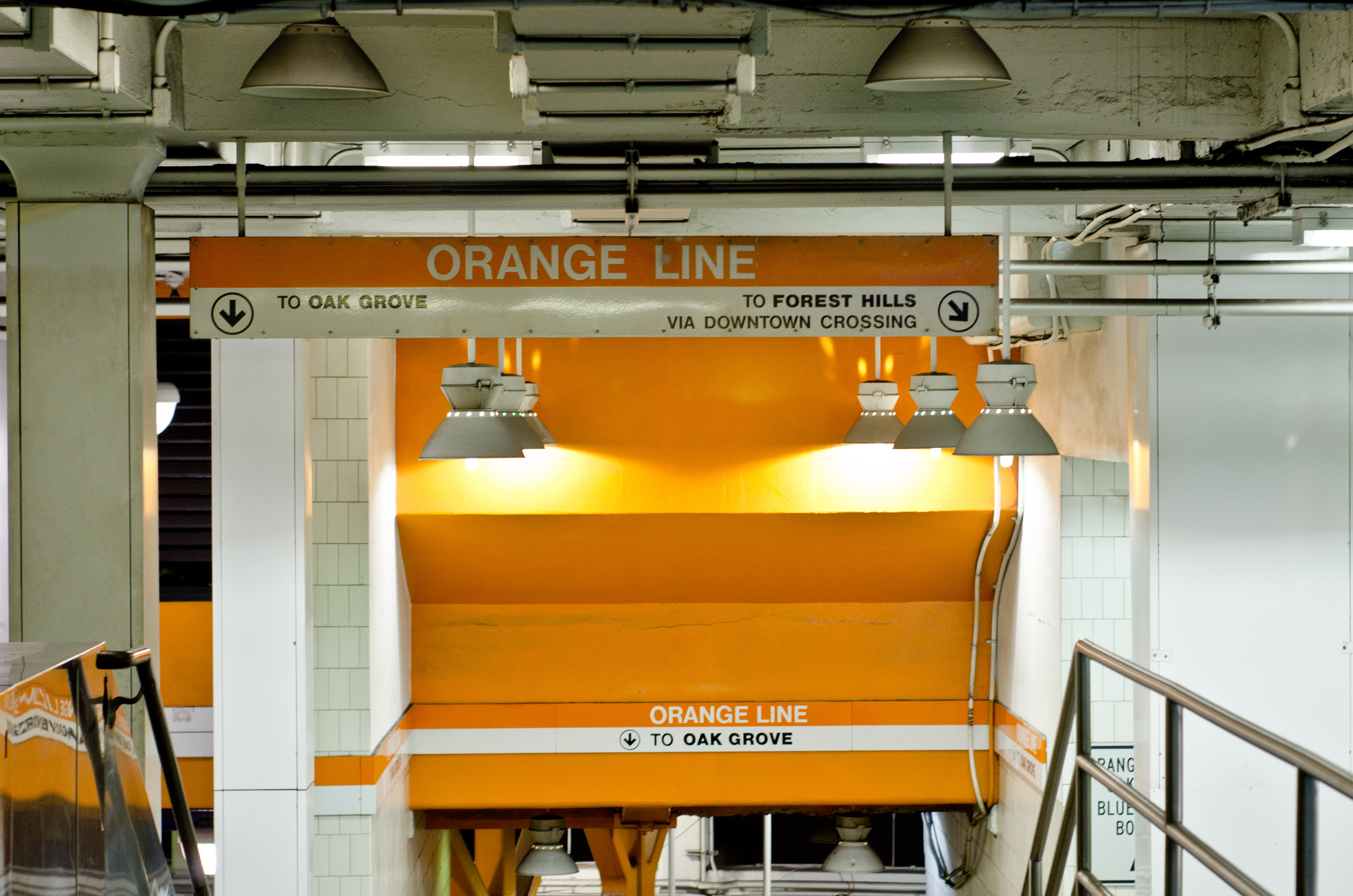 The interior of the Orange Line Station in Boston. The walls are orange and white. There is a staircase.