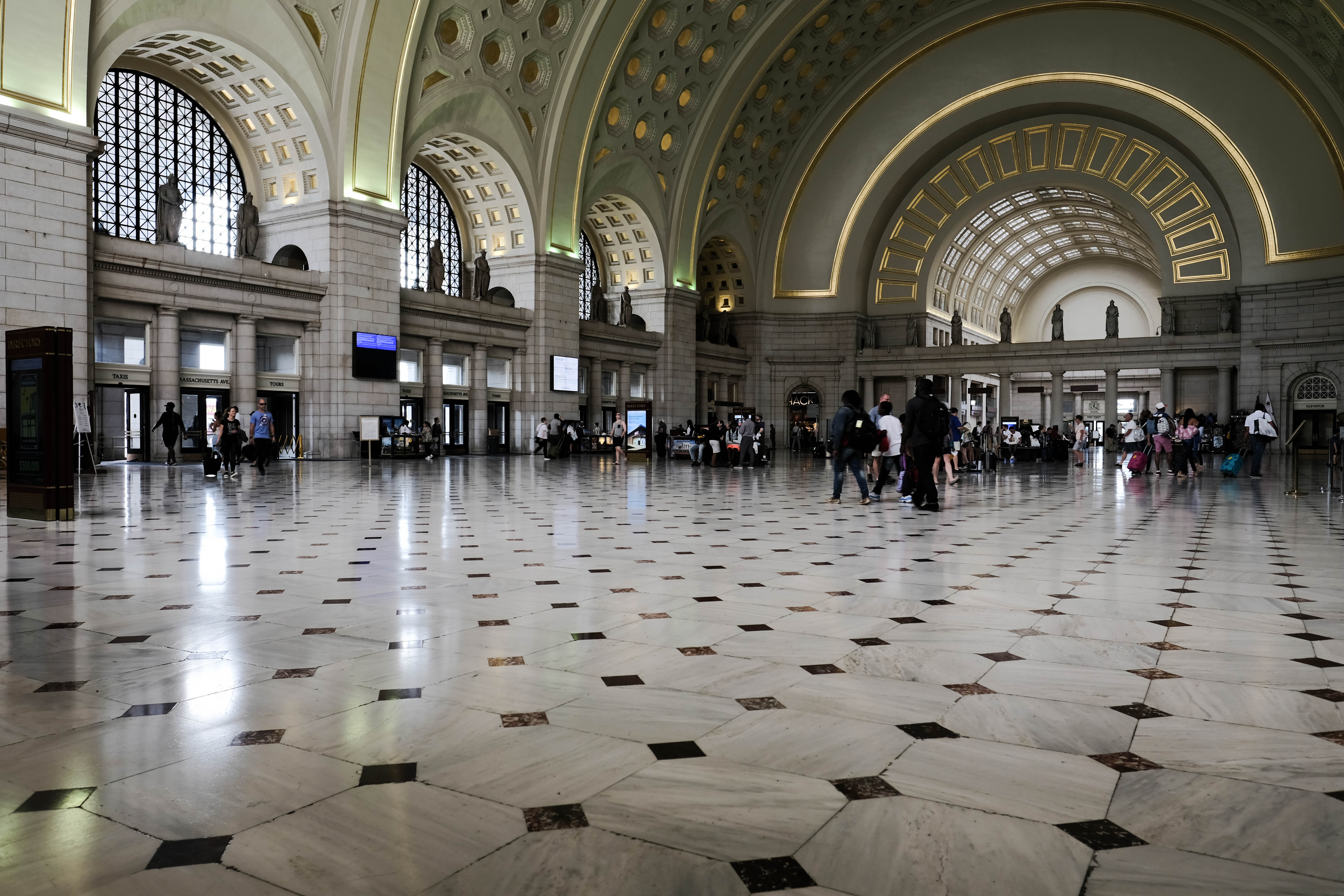 The interior of Union Station in Washington D.C. The floor has black and white patterned tiles. The ceiling is arched.