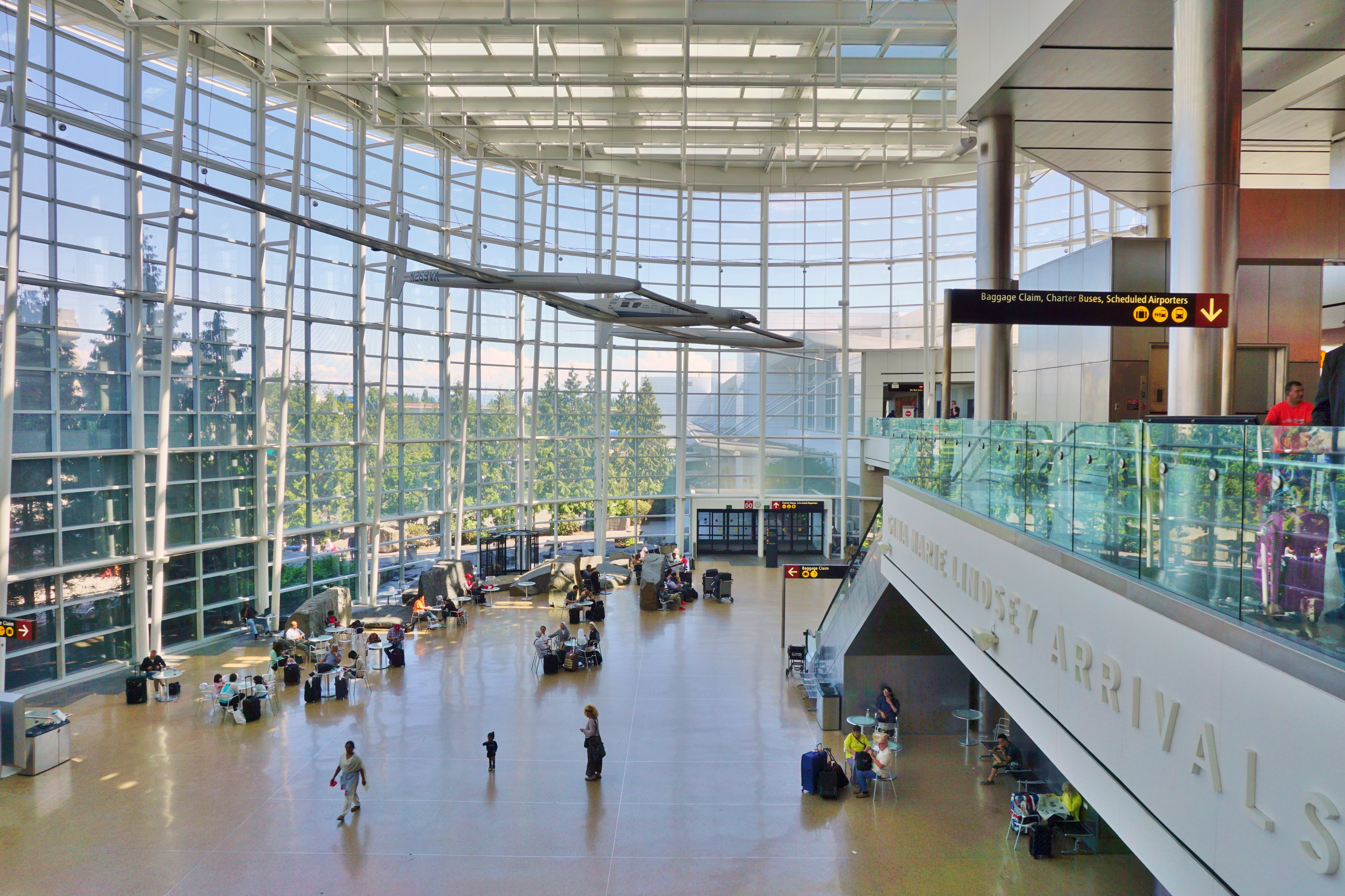 The interior of Sea-Tac Airport in Seattle. There is a high ceiling and floor to ceiling windows. Outside there are many tall trees. There are two levels and people walking on the lower level near the windows.
