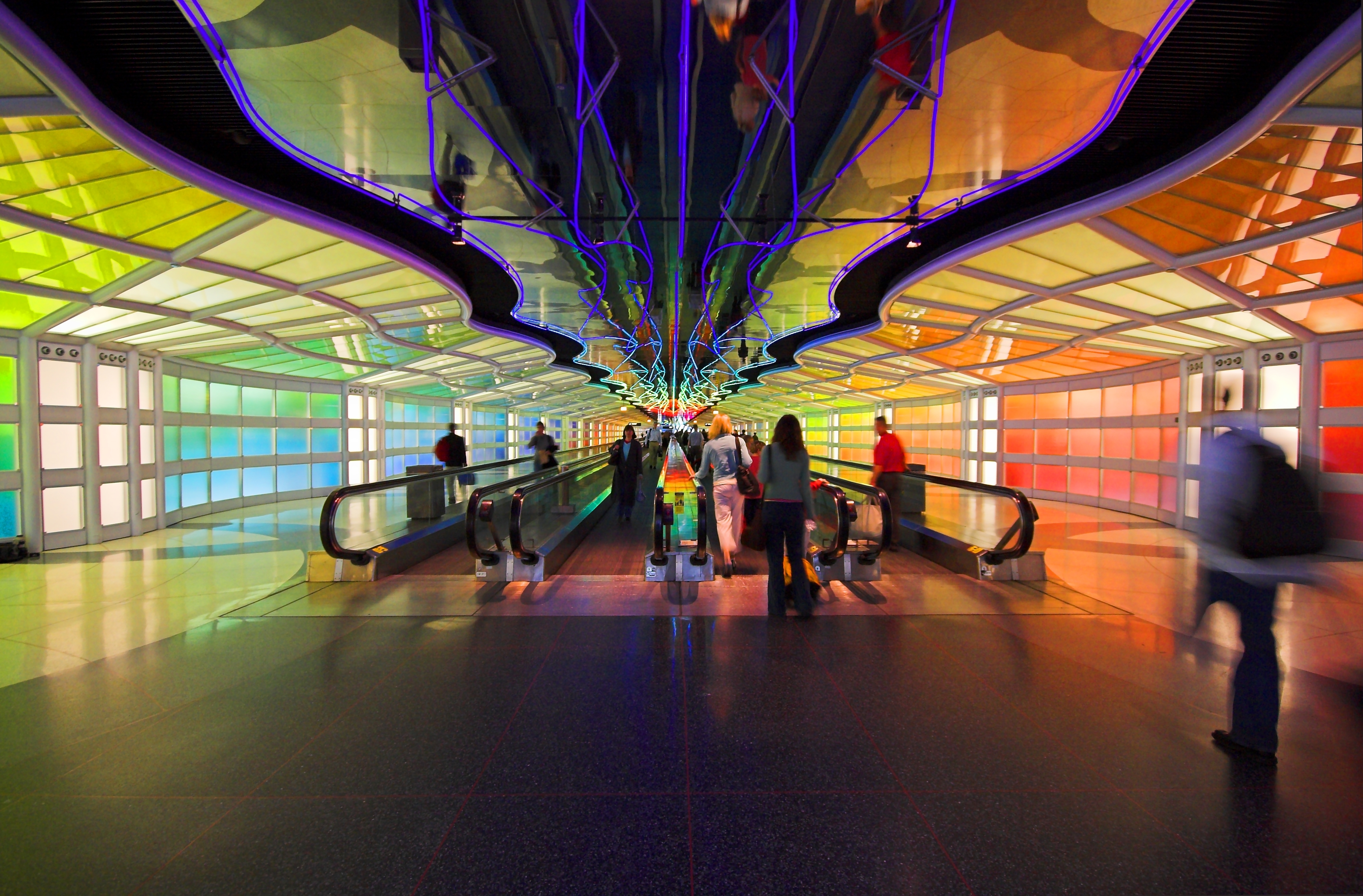 The interior of the Terminal 1 tunnel in the Chicago O'Hare airport. The walls are multicolored.