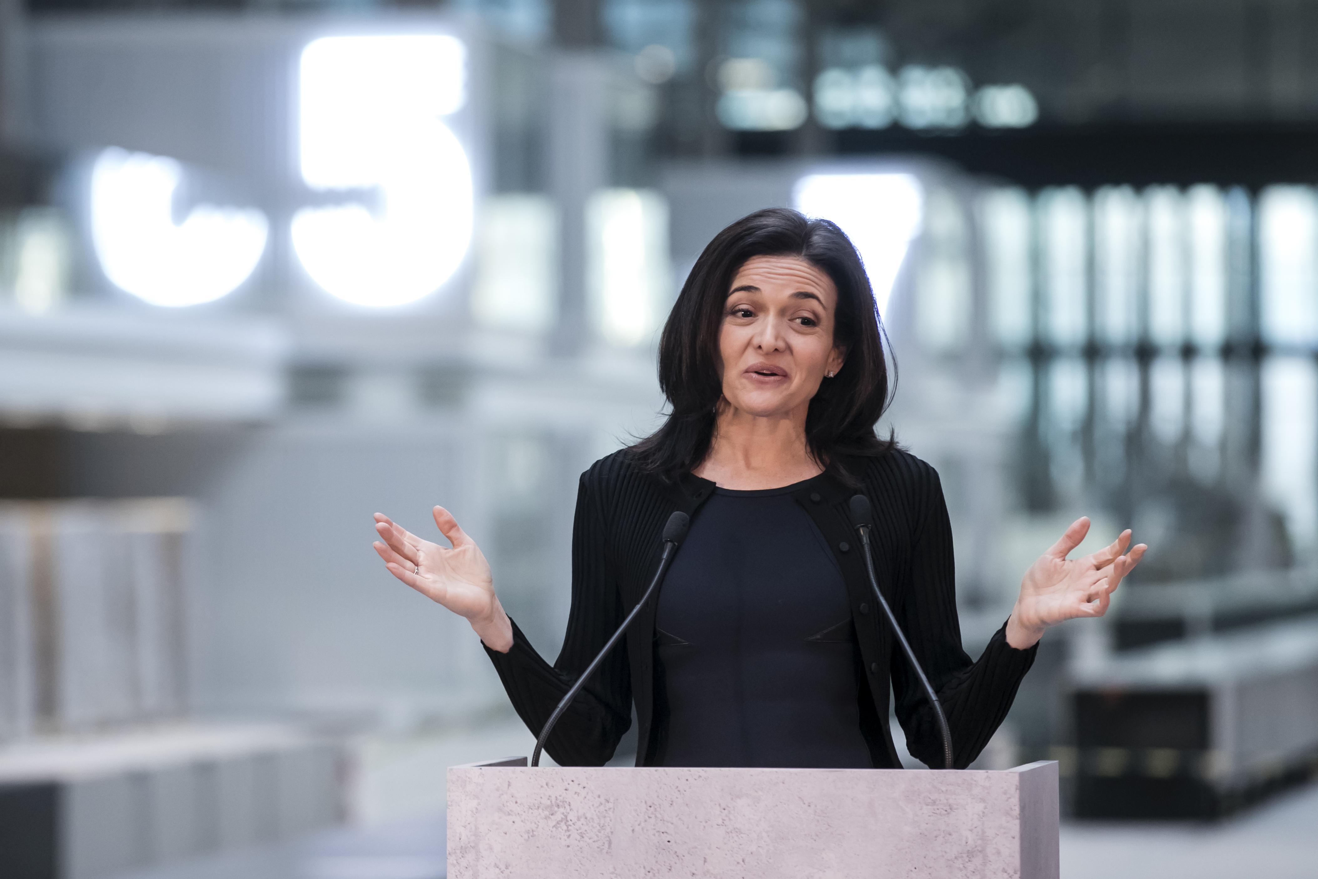 Facebook COO Sheryl Sandberg speaking at a podium