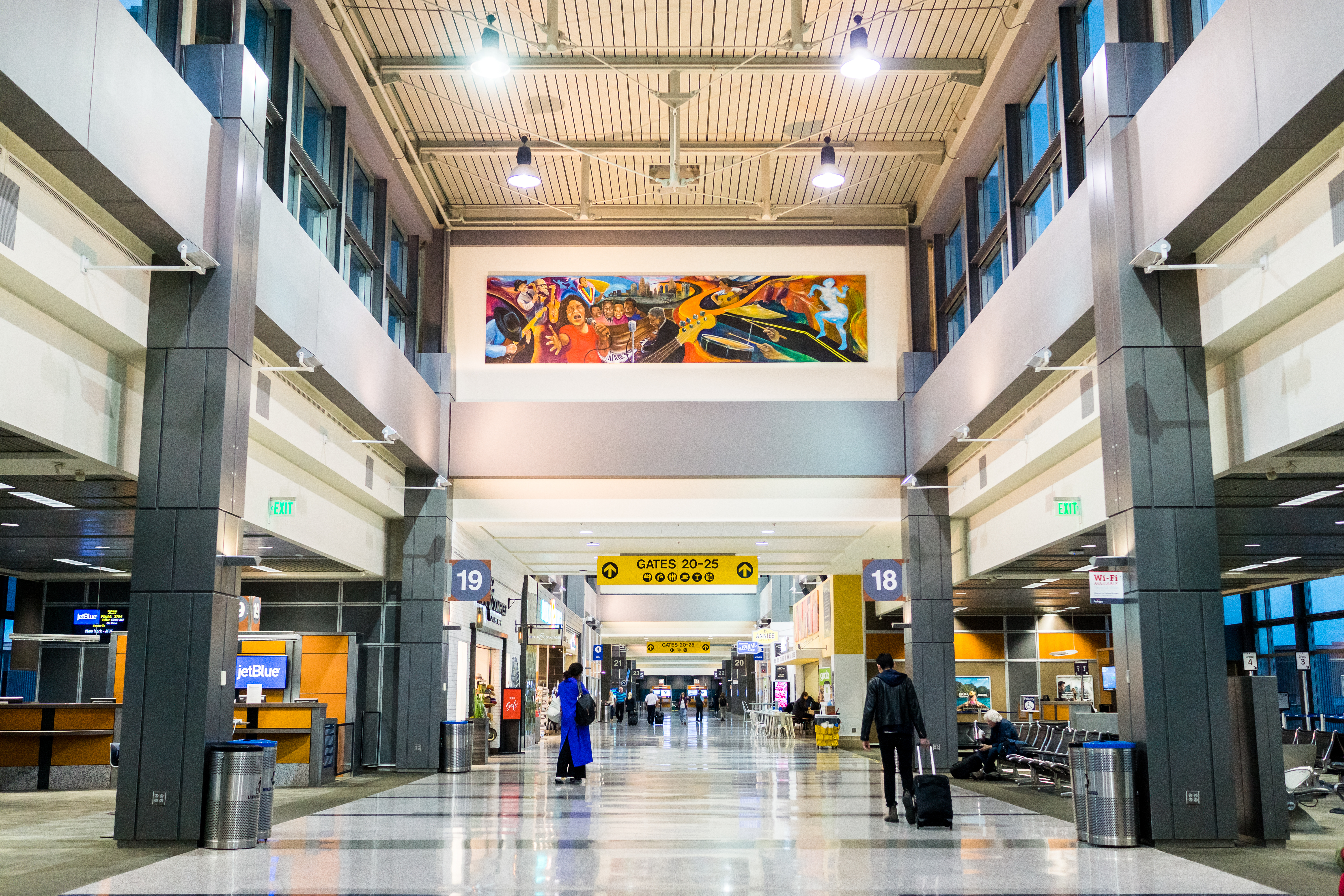 The interior of the Austin-Bergstrom International Airport. There is a high ceiling and two levels of shops and airport gates.