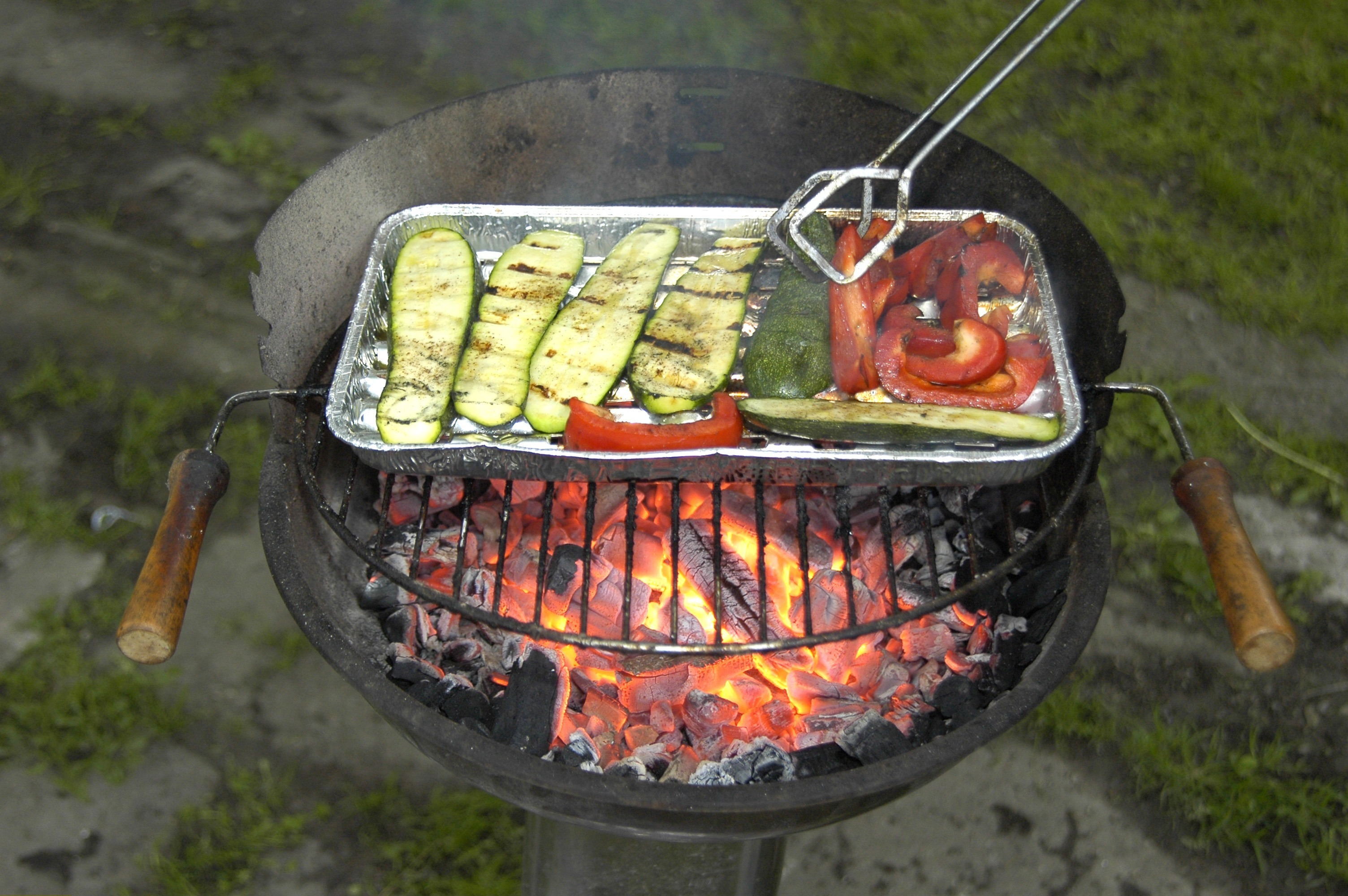 A tray full of vegetables roasts on an outdoor barbecue.