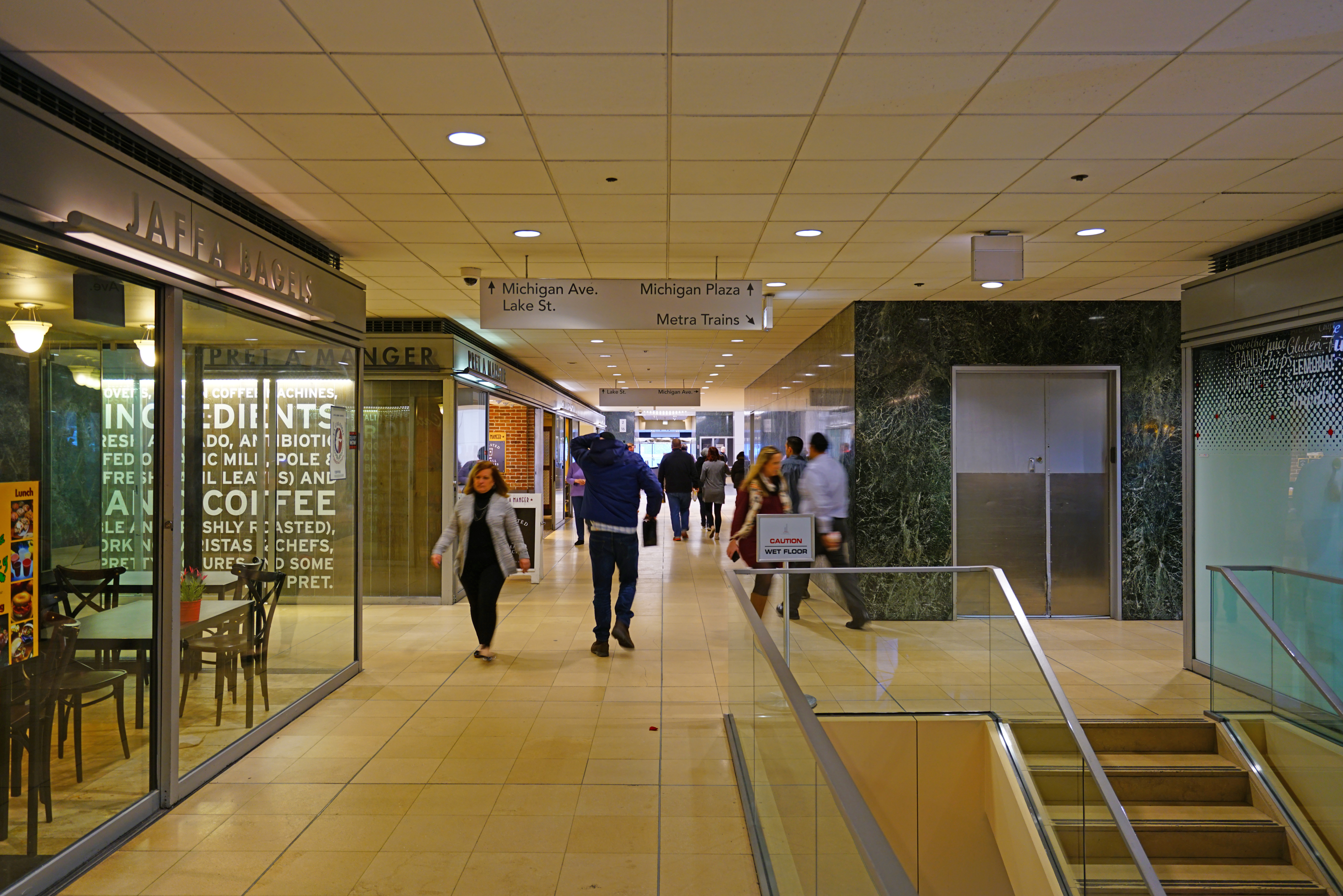 A hallway with a white floor and white ceiling. Shops on the left and right with a few people walking down a hall. A staircase and elevator shown on the right.
