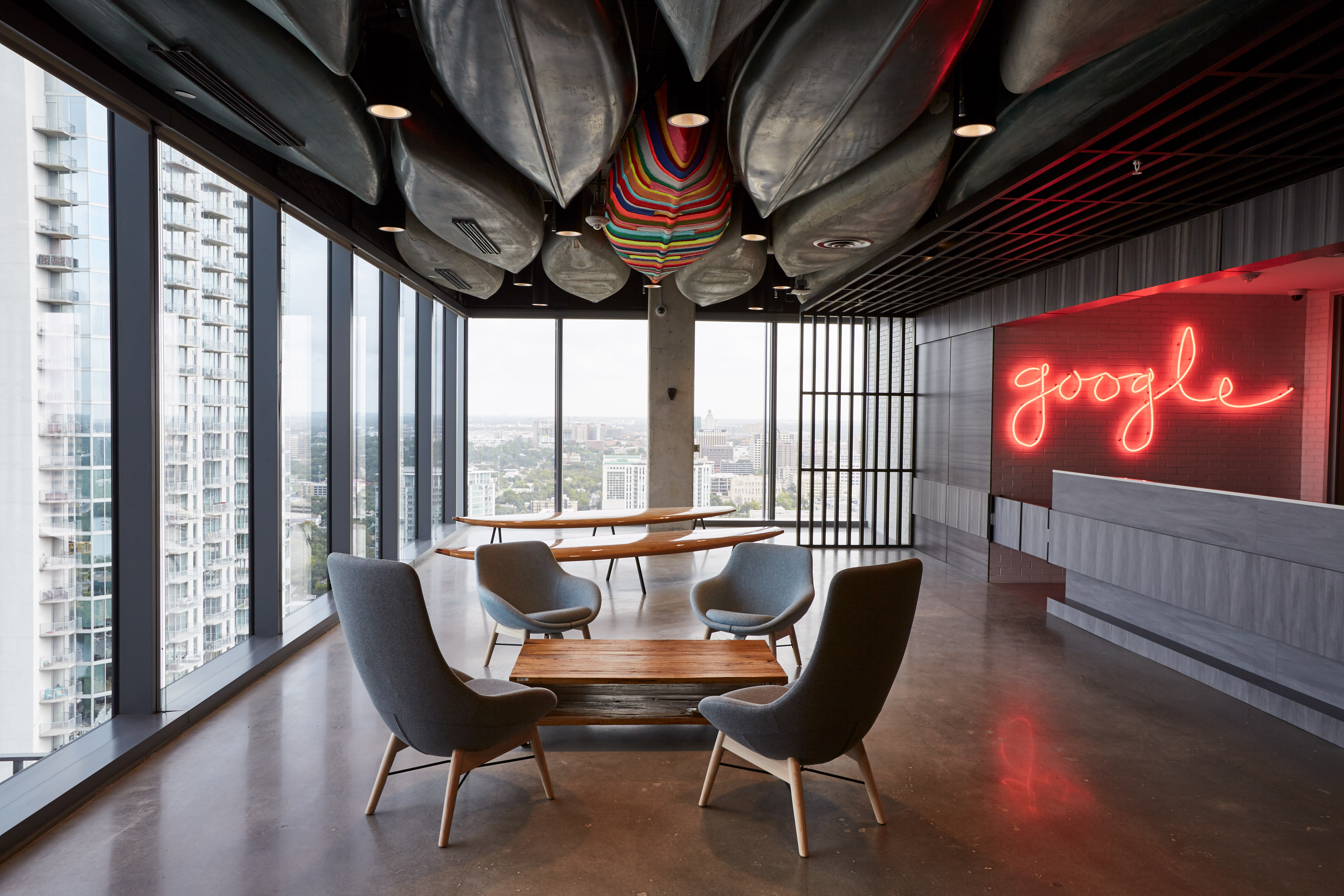 """room in high-rise with window walls and canoes on the ceiling and a neon sign that says """"google"""" in script"""