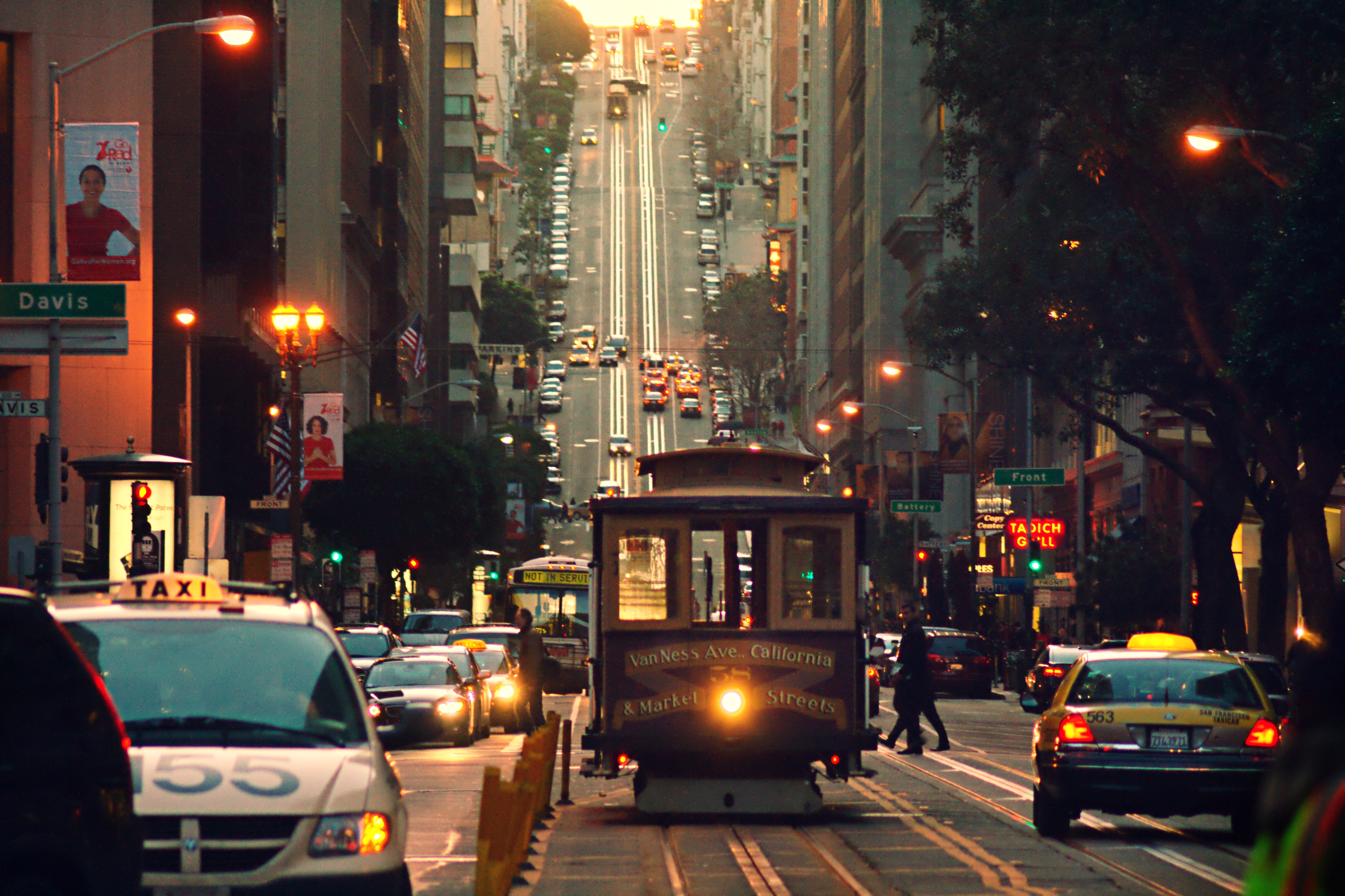 A crowded SF street, with cars, a cable car, and pedestrians.
