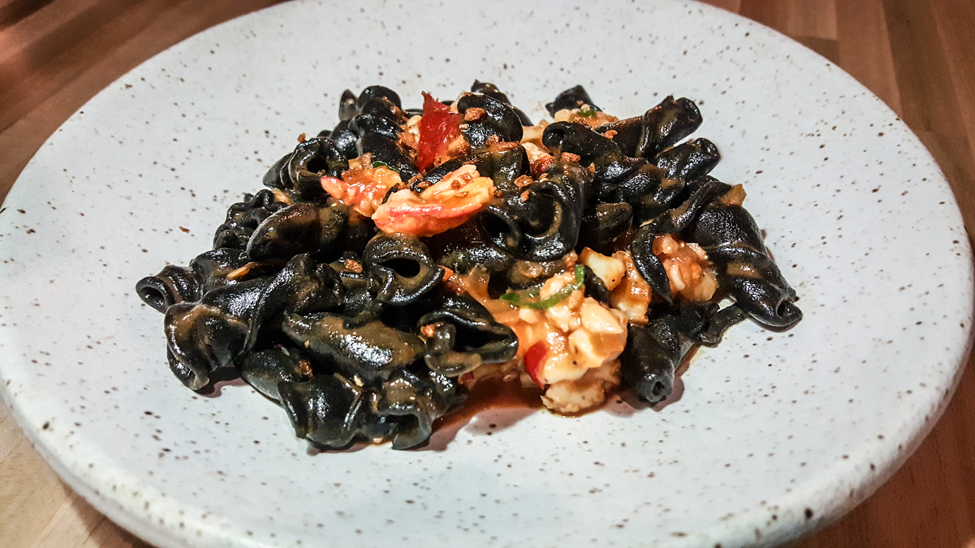 Black campanelle pasta with chunks of lobster on an earthy, white-speckled plate