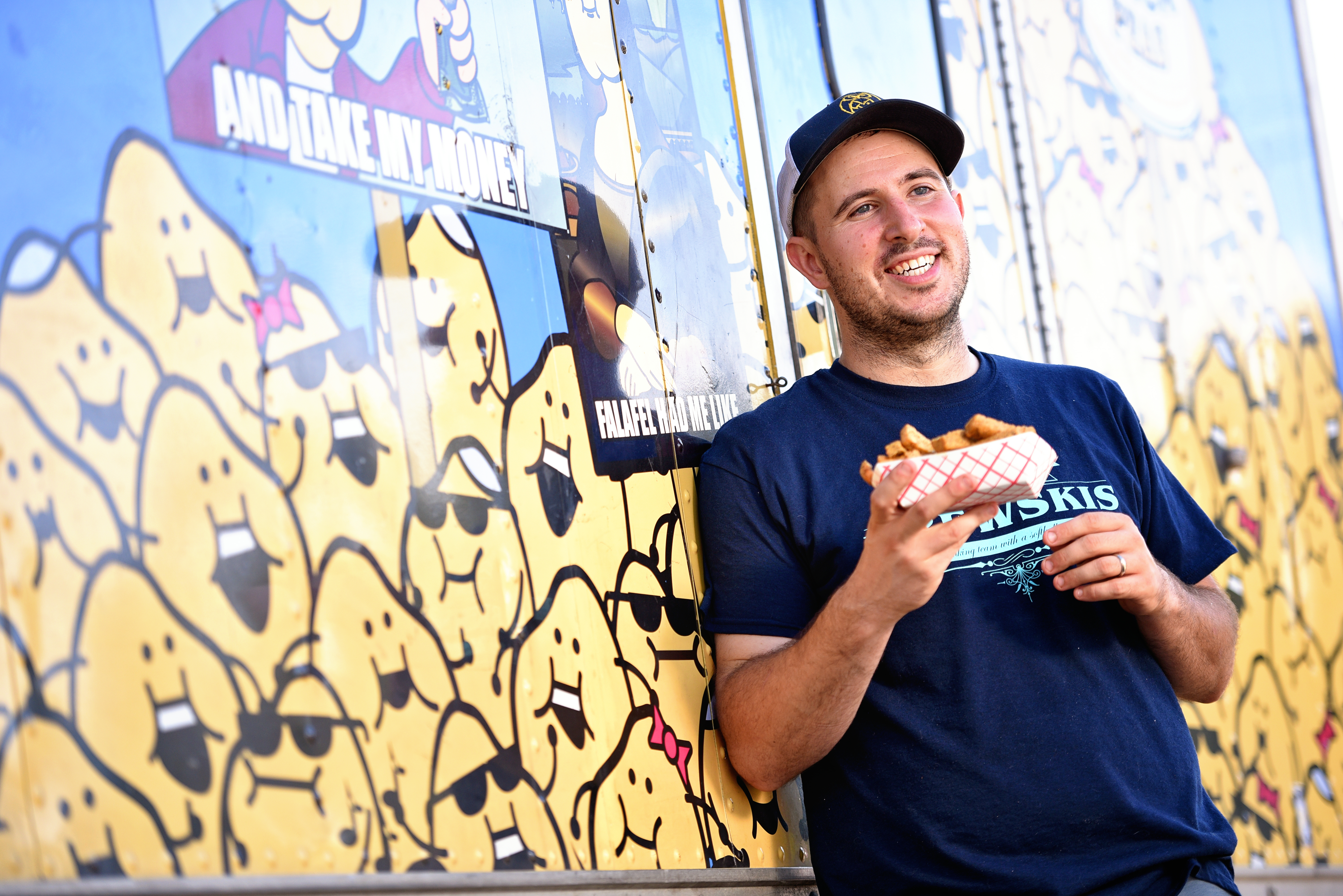 Avi Shemtov in front of his Chubby Chickpea truck, holding chickpea fries