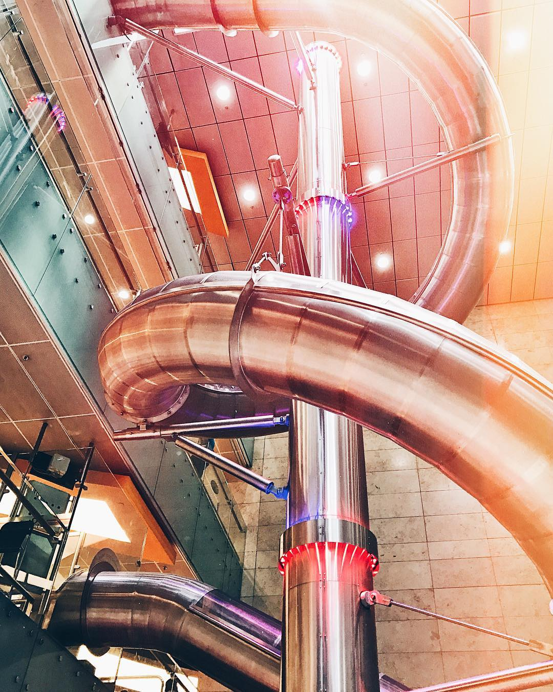 A view of the slide at Changi International Airport in Singapore. The slide is suspended from a high ceiling.