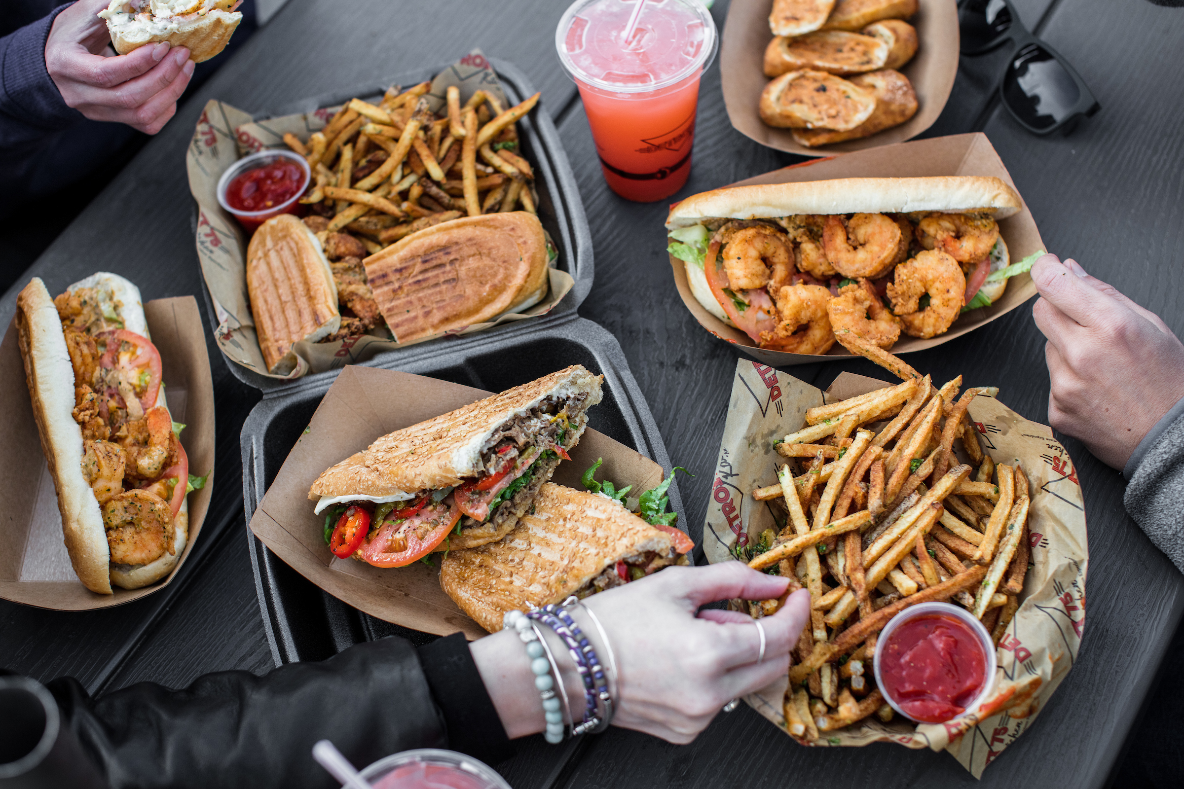 Hands reach for fries across a table that's covered in black carryout containers filled with fries, pressed sandwiches, and shrimp sandwiches.