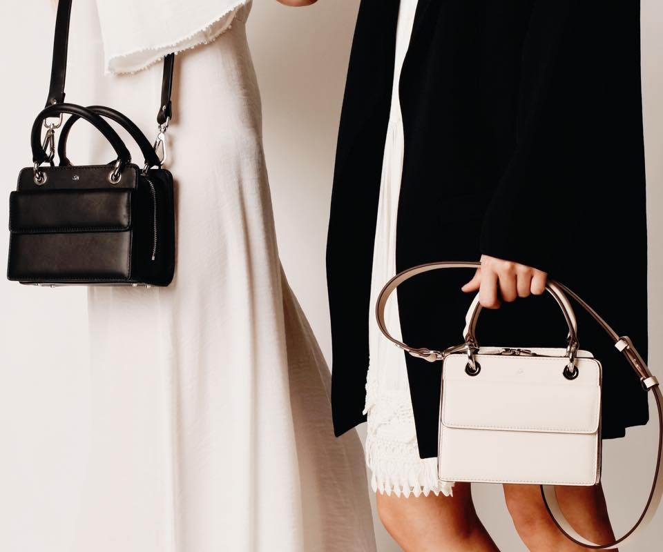 Two women holding handbags from the brand 324