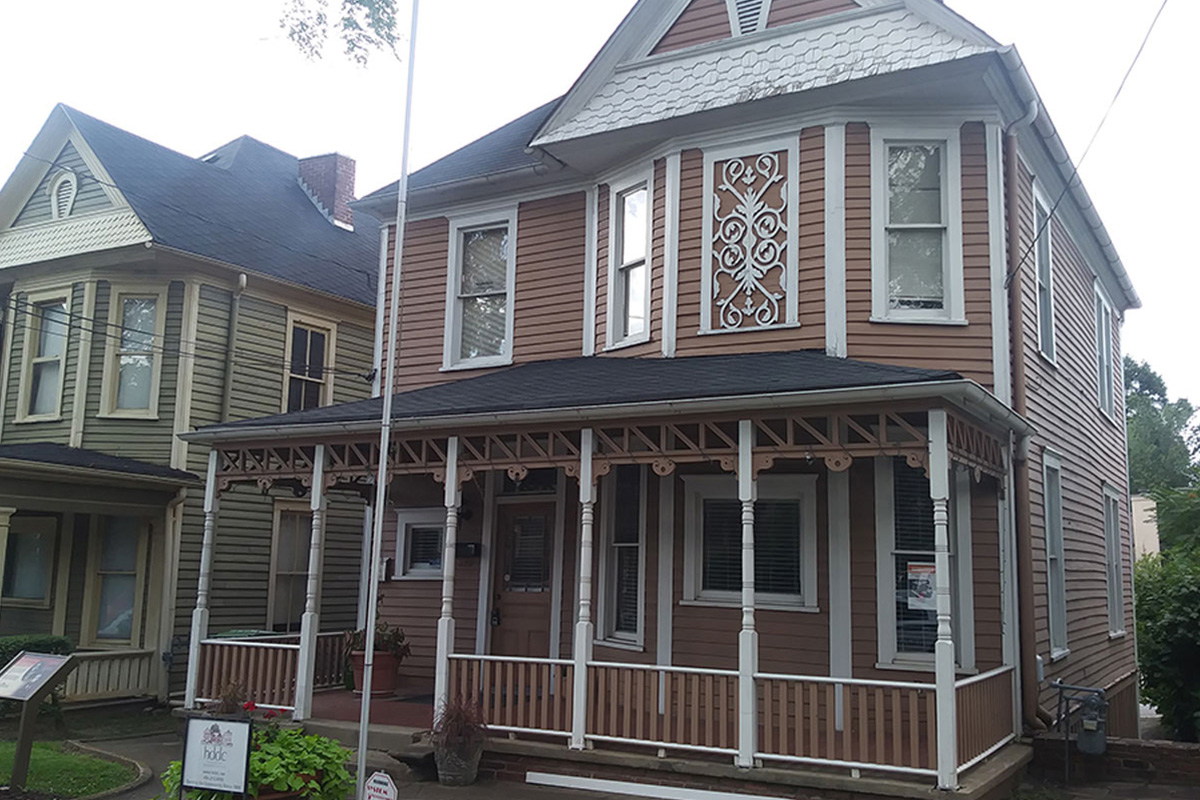 A classical house with brown siding and a front porch.