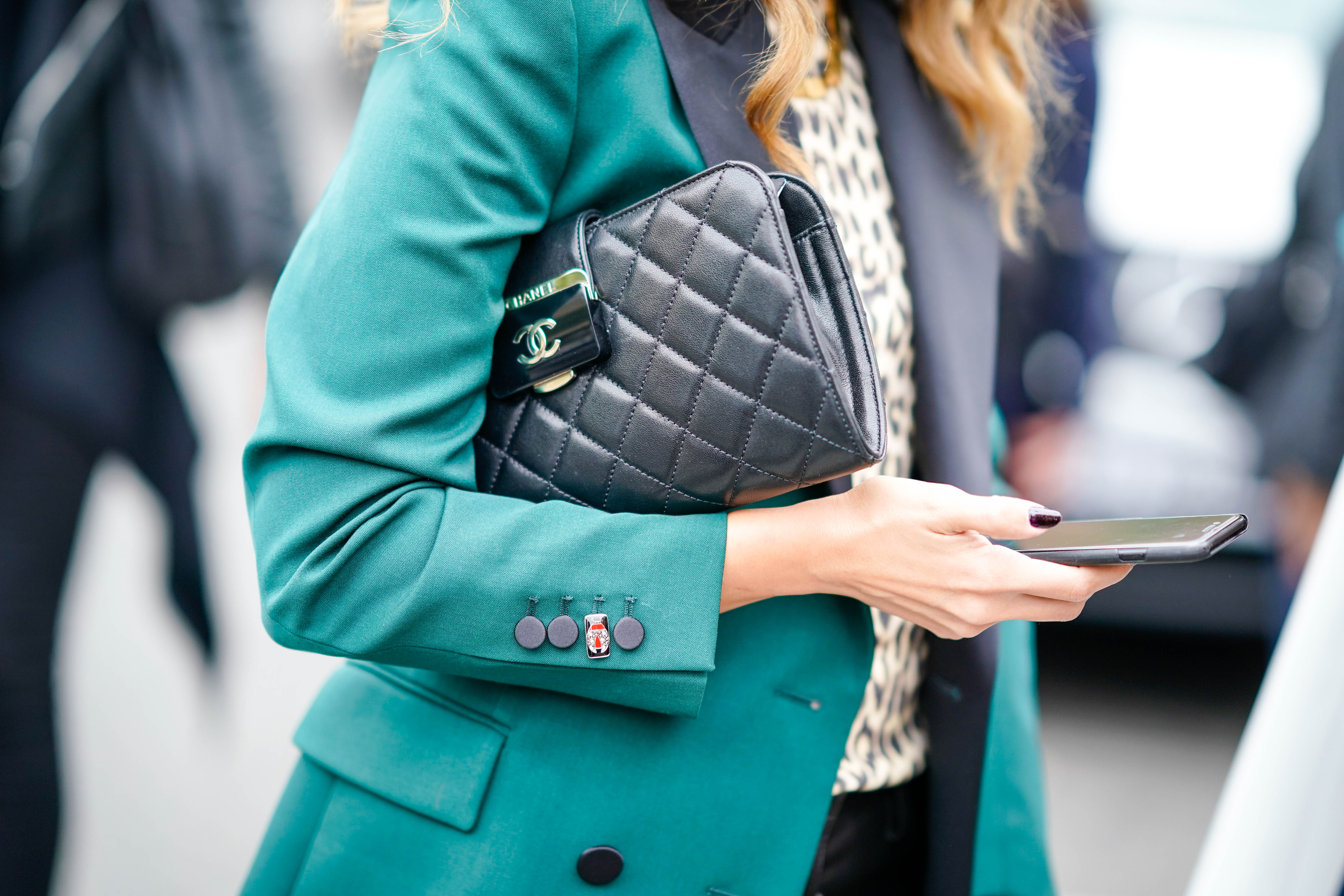 A woman holding a cell phone and a Chanel purse.