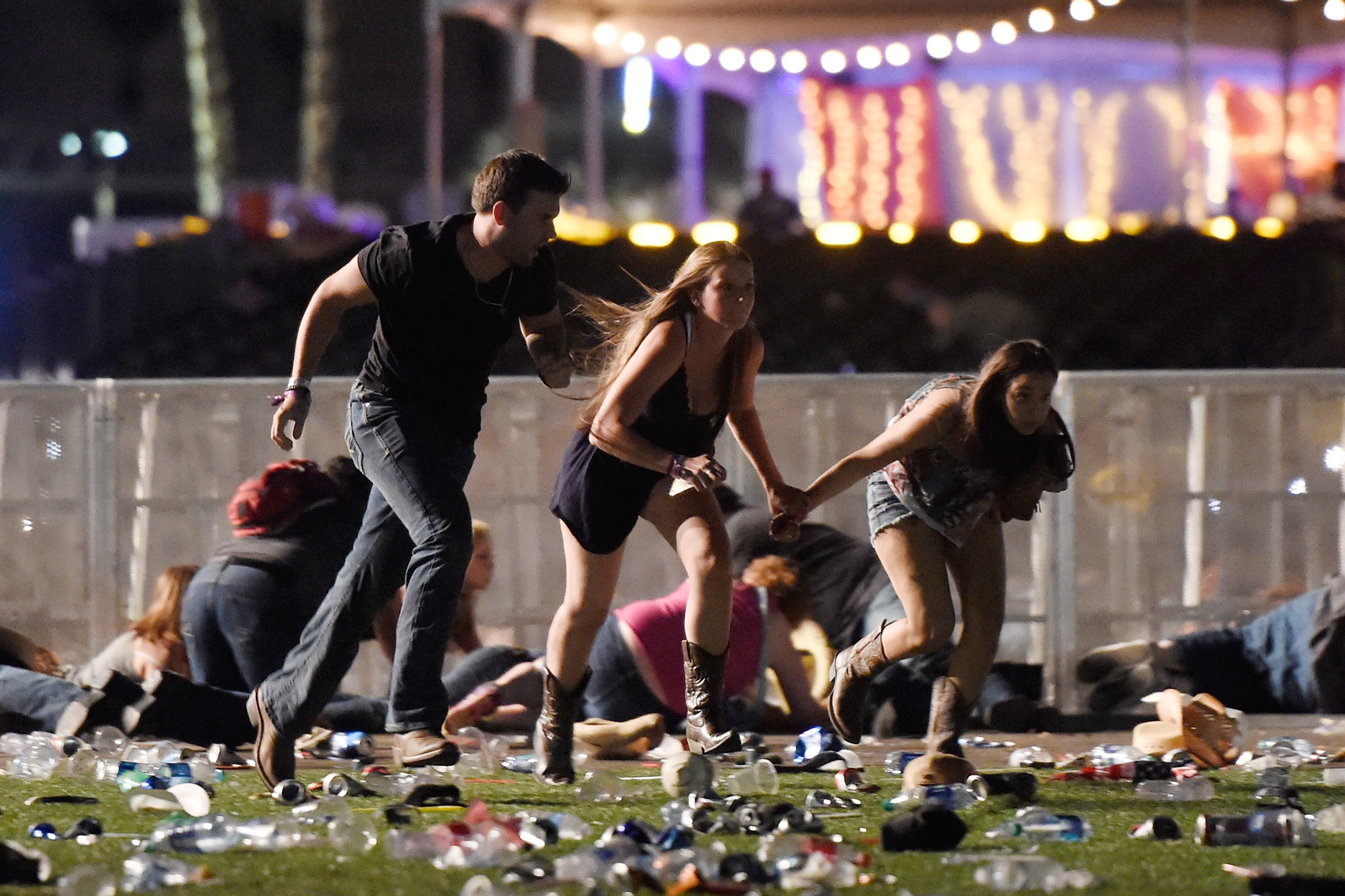 People run from the Route 91 Harvest country music festival after gunfire was heard on October 1, 2017, in Las Vegas, Nev. A gunman has opened fire on a music festival in Las Vegas, leaving at least 20 people dead and more than 100 injured. Polic