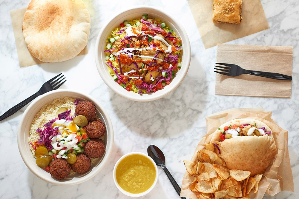 A table spread of dishes, which includes a pita sandwich, a falafel hummus bowl, a chicken rice bowl, and a baklava square