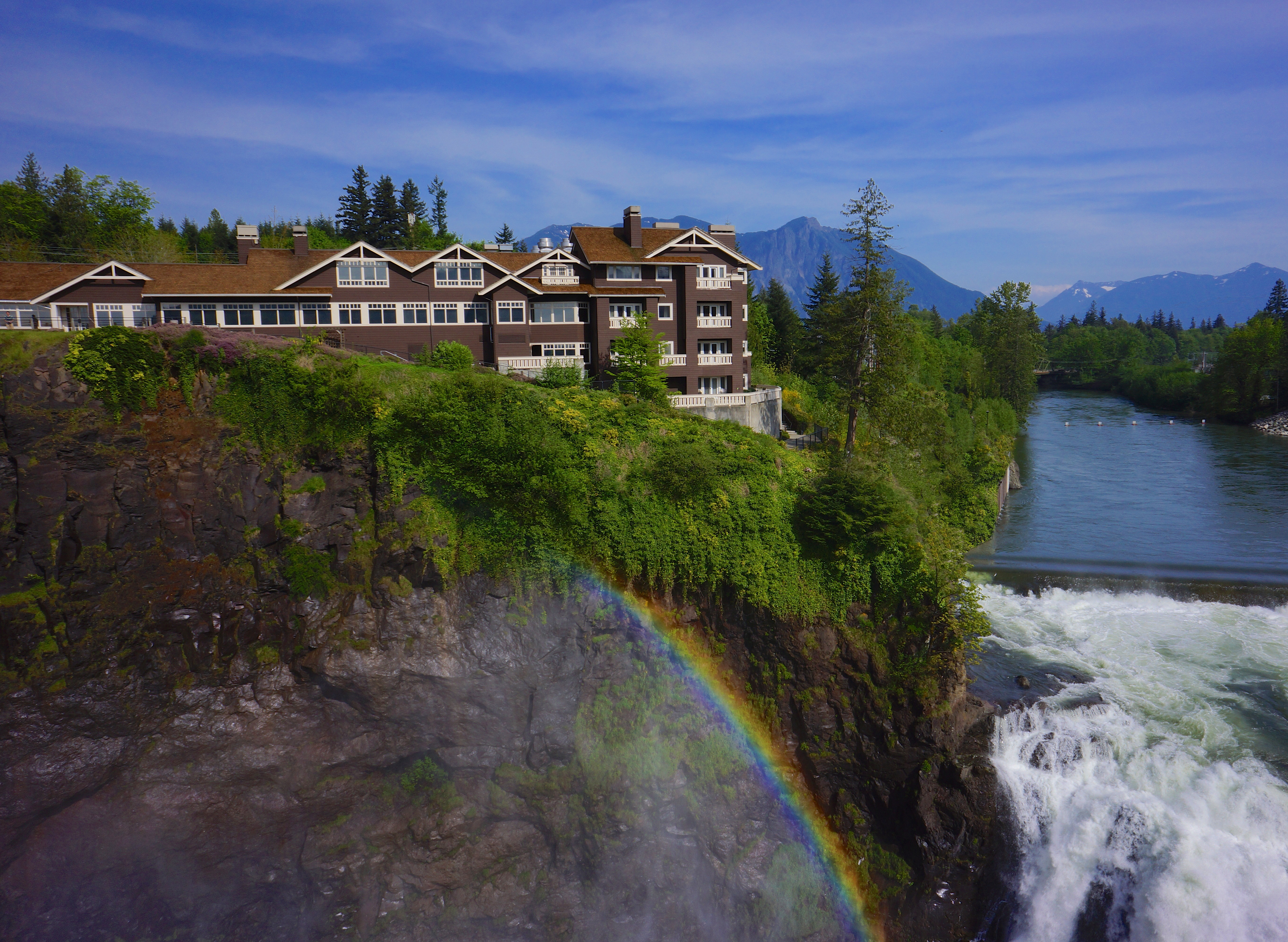 A cliff edge with a rainbow in Snoqualmie. At the edge of the cliff is a waterfall and trees. There are houses on the cliff and mountains in the distance.