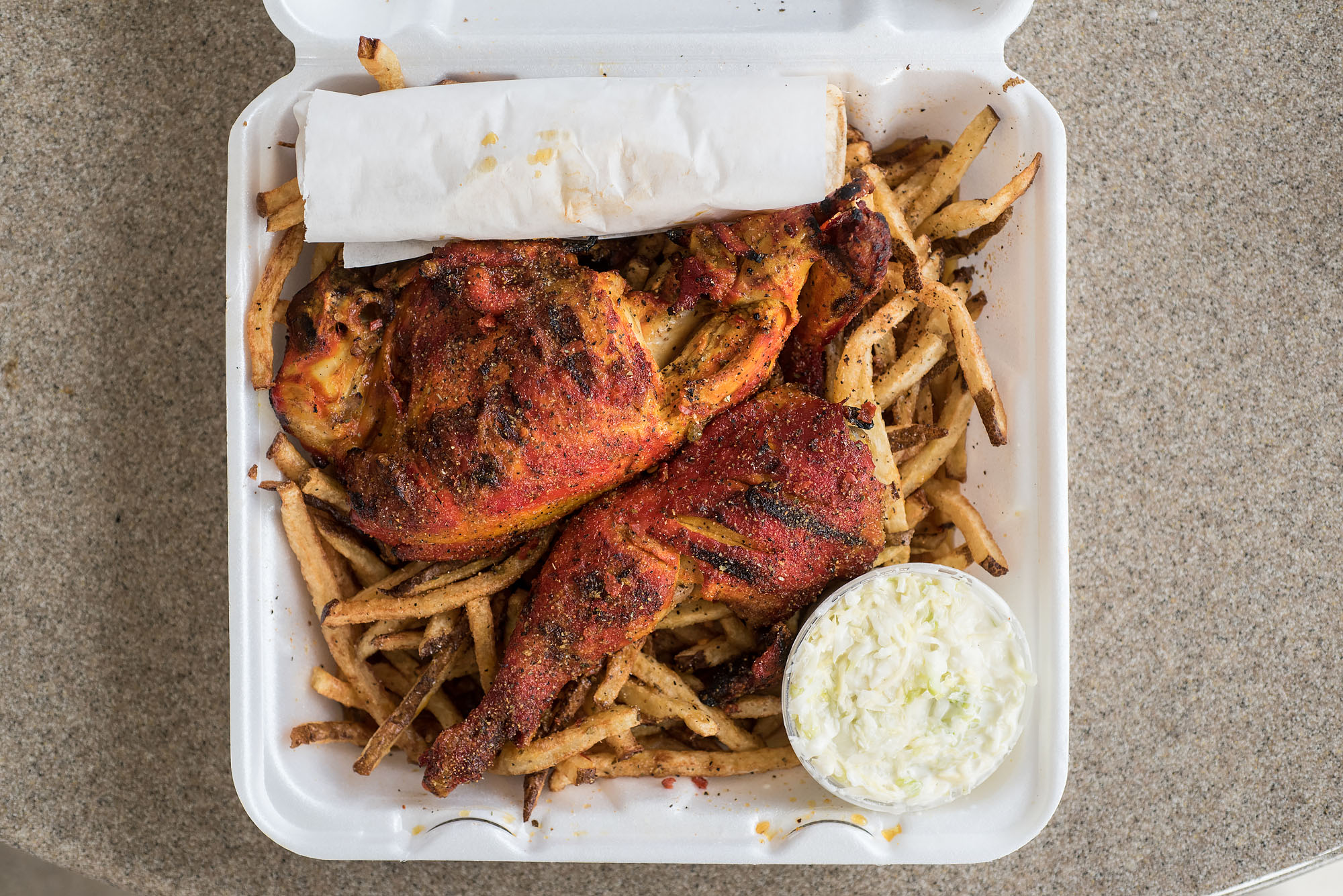 An overhead shot of red sauced grilled chicken atop fries in a takeout container.