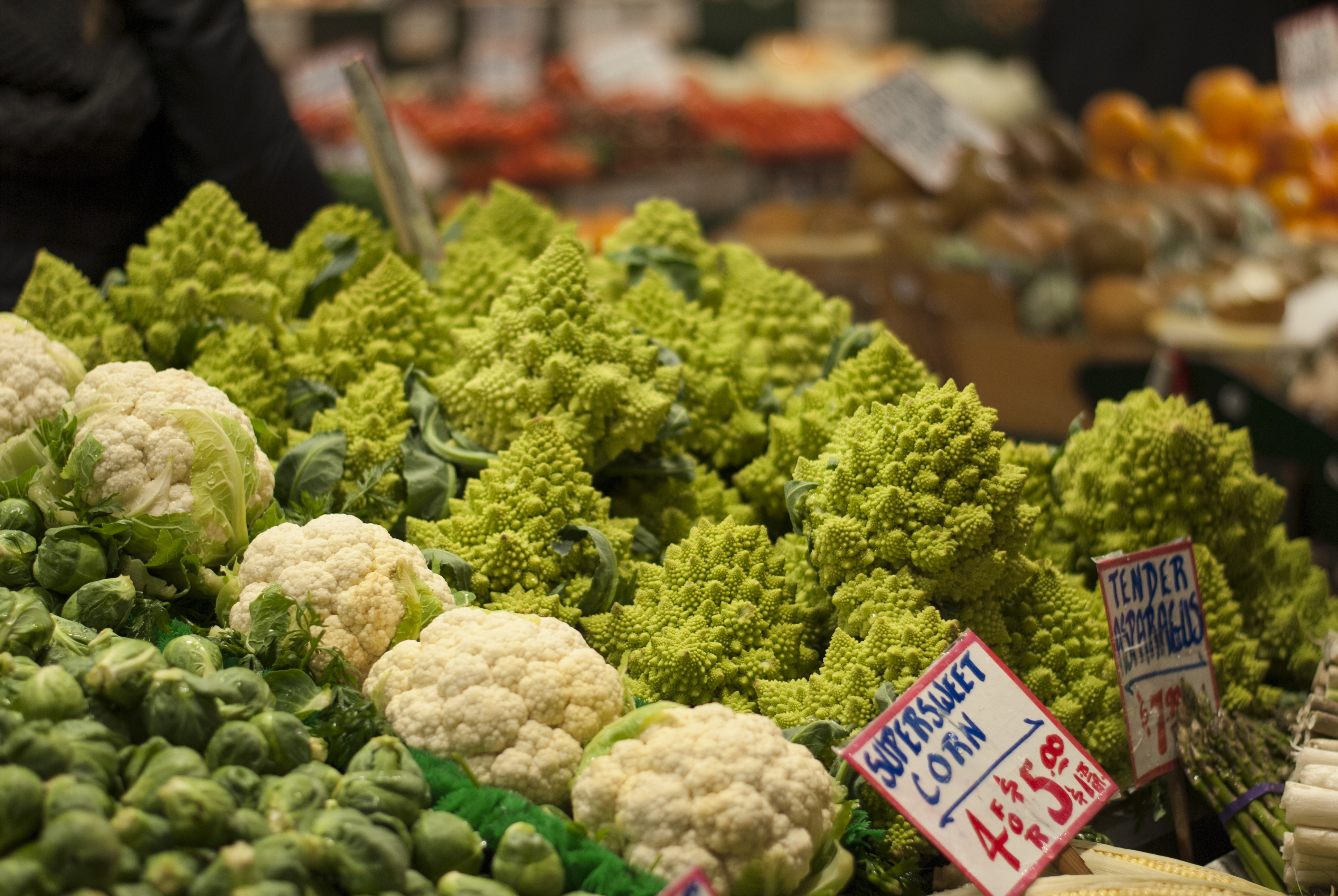 Left to right, Brussels sprouts, cauliflower, and romanesco sit in a market display stand. There are more stands in the background, which are out of focus.