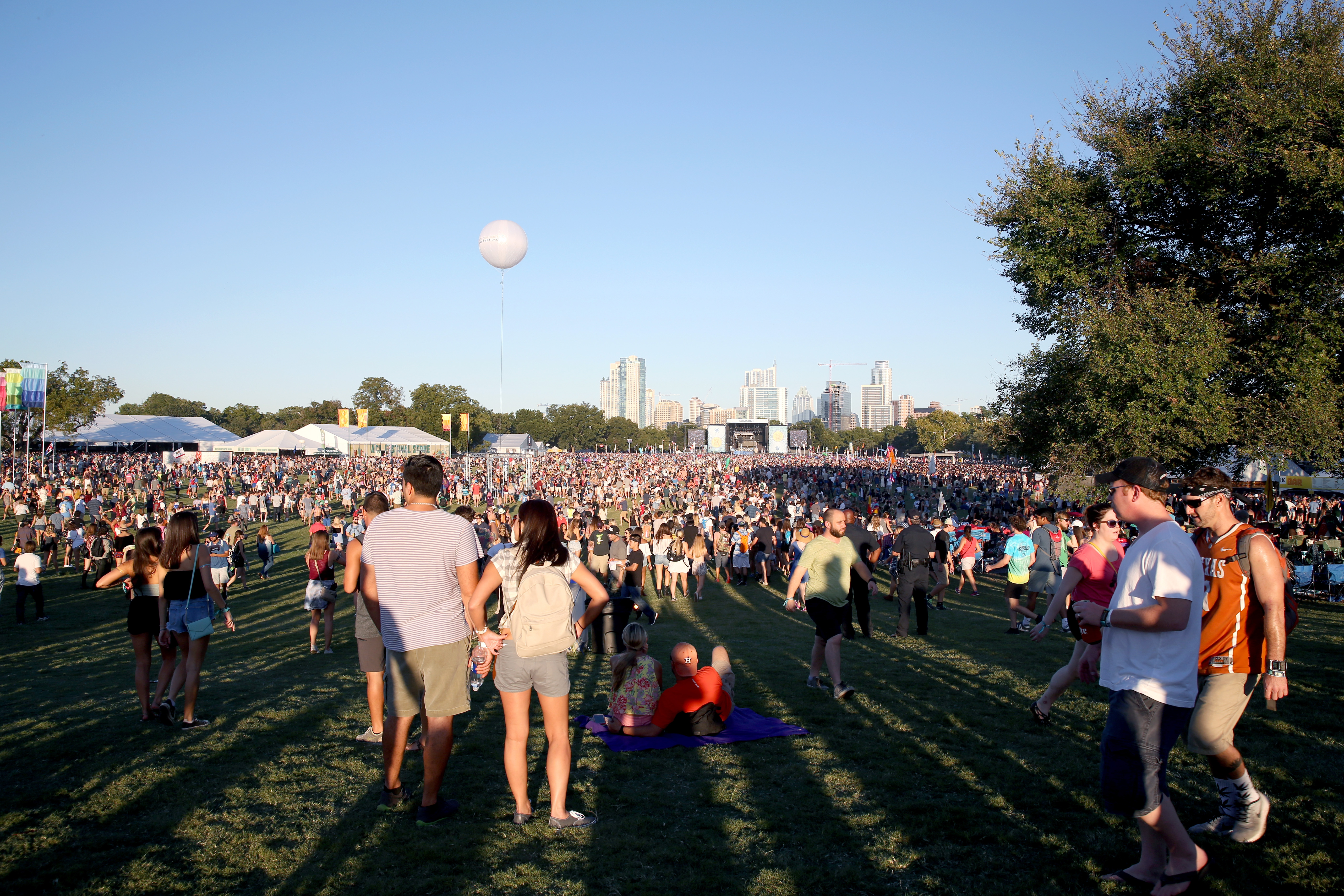 A large crowd in an Austin park with a stage in the distance, daytime