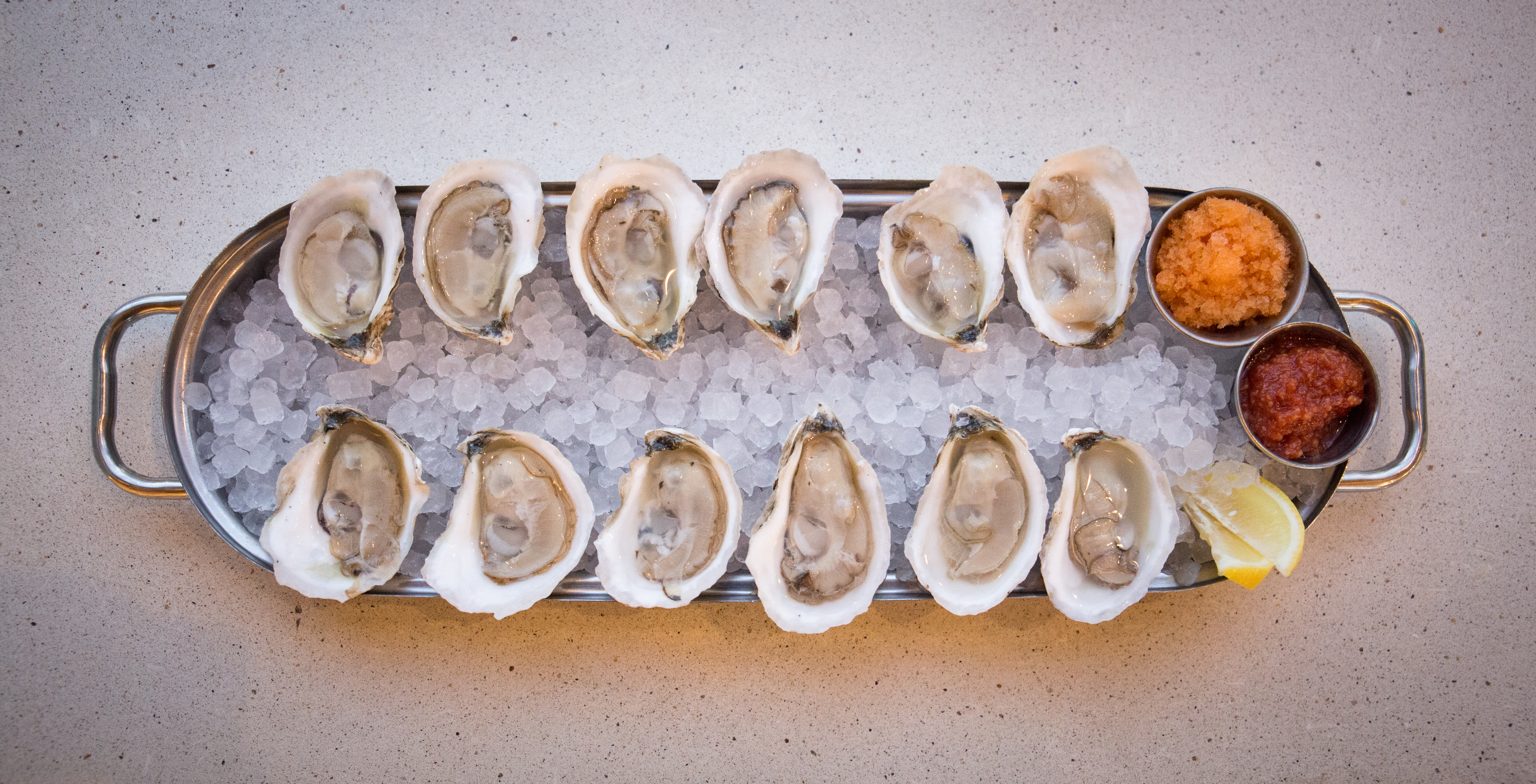 Overhead view of a dozen oysters on ice on an elongated silver tray with sauces and a lemon wedge