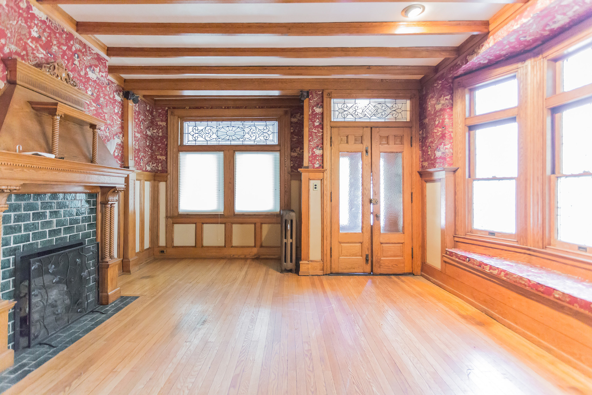 The foyer of a Victorian home with exposed beams, hardwoods, stained glass windows, a fireplace, and original woodwork.