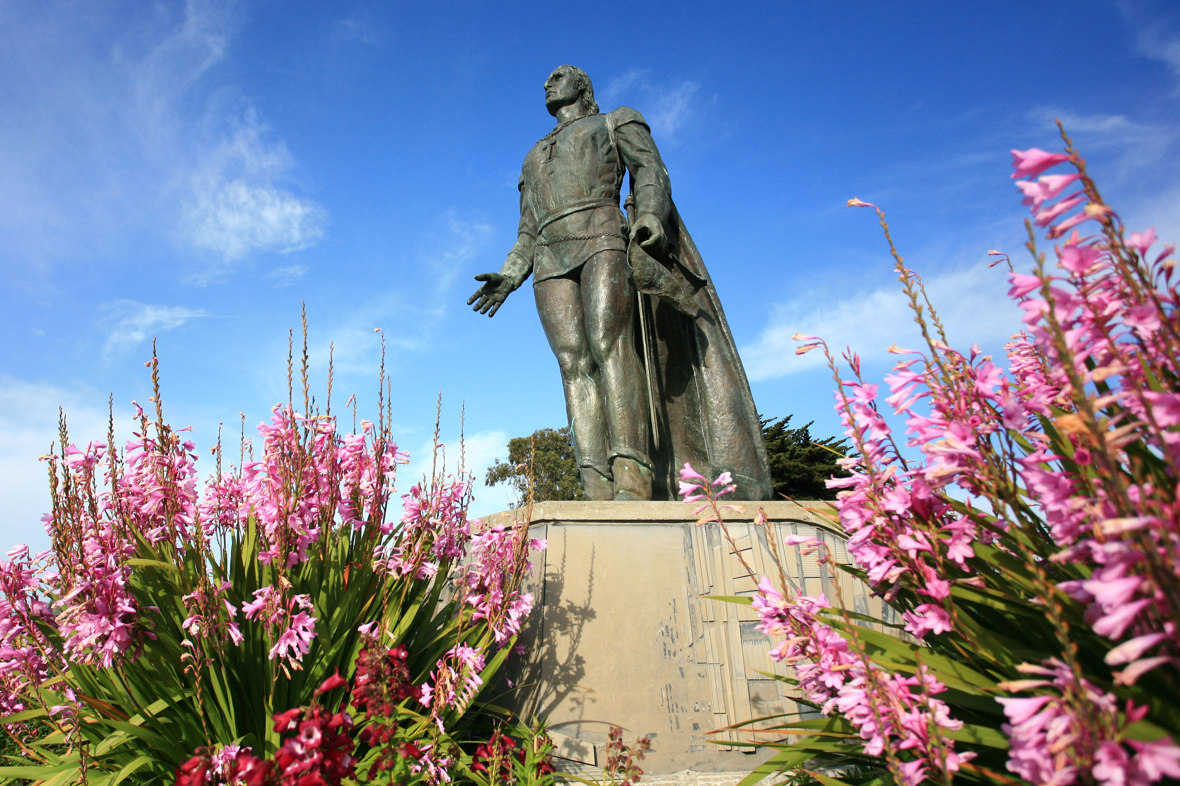 A low-angle photo of the Columbus Statue next to Coit Tower with a blue sky in the background.
