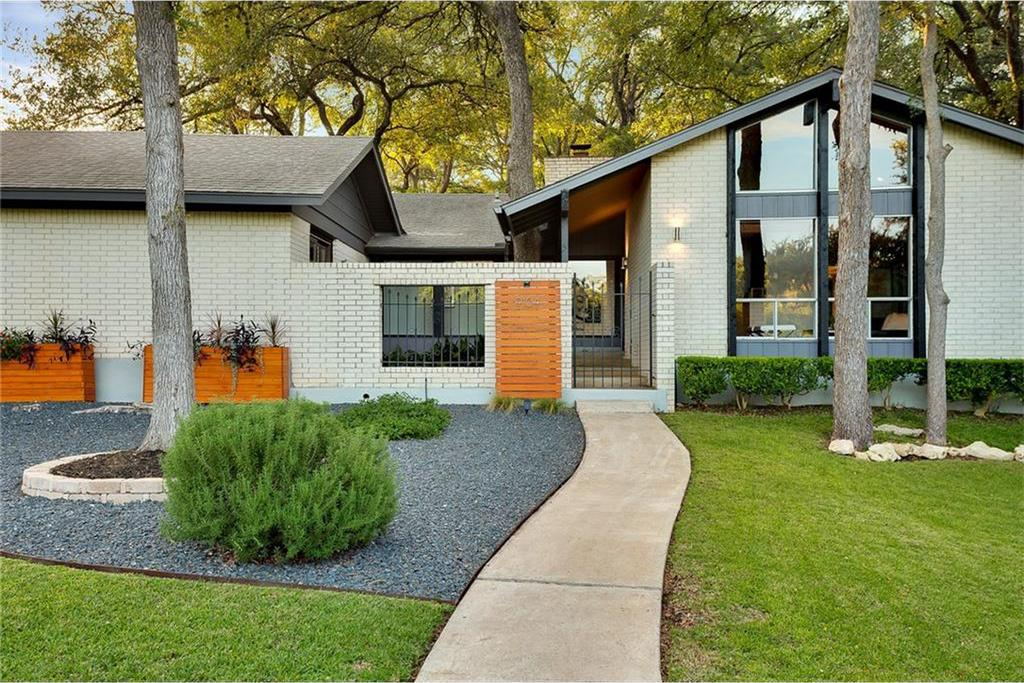 Large white brick 1970s ranch home