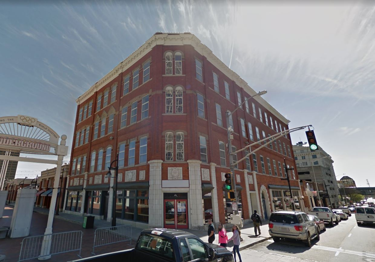 A four-story brick building with retail spaces at ground floor.