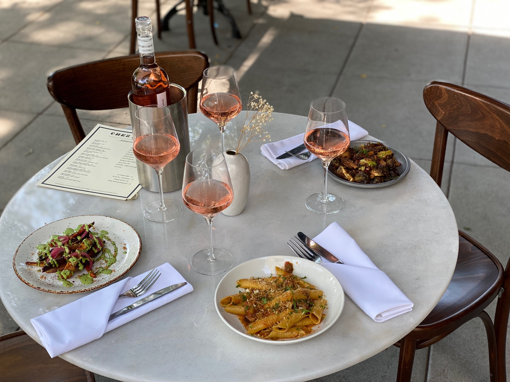 An outdoor dining table with four glasses of rosé, three bowls of pasta, and two dark wooden chairs pulled up.