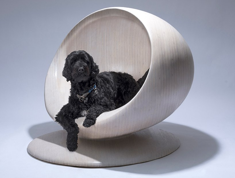 Orb-like wooden house on pedestal with dog inside of it.