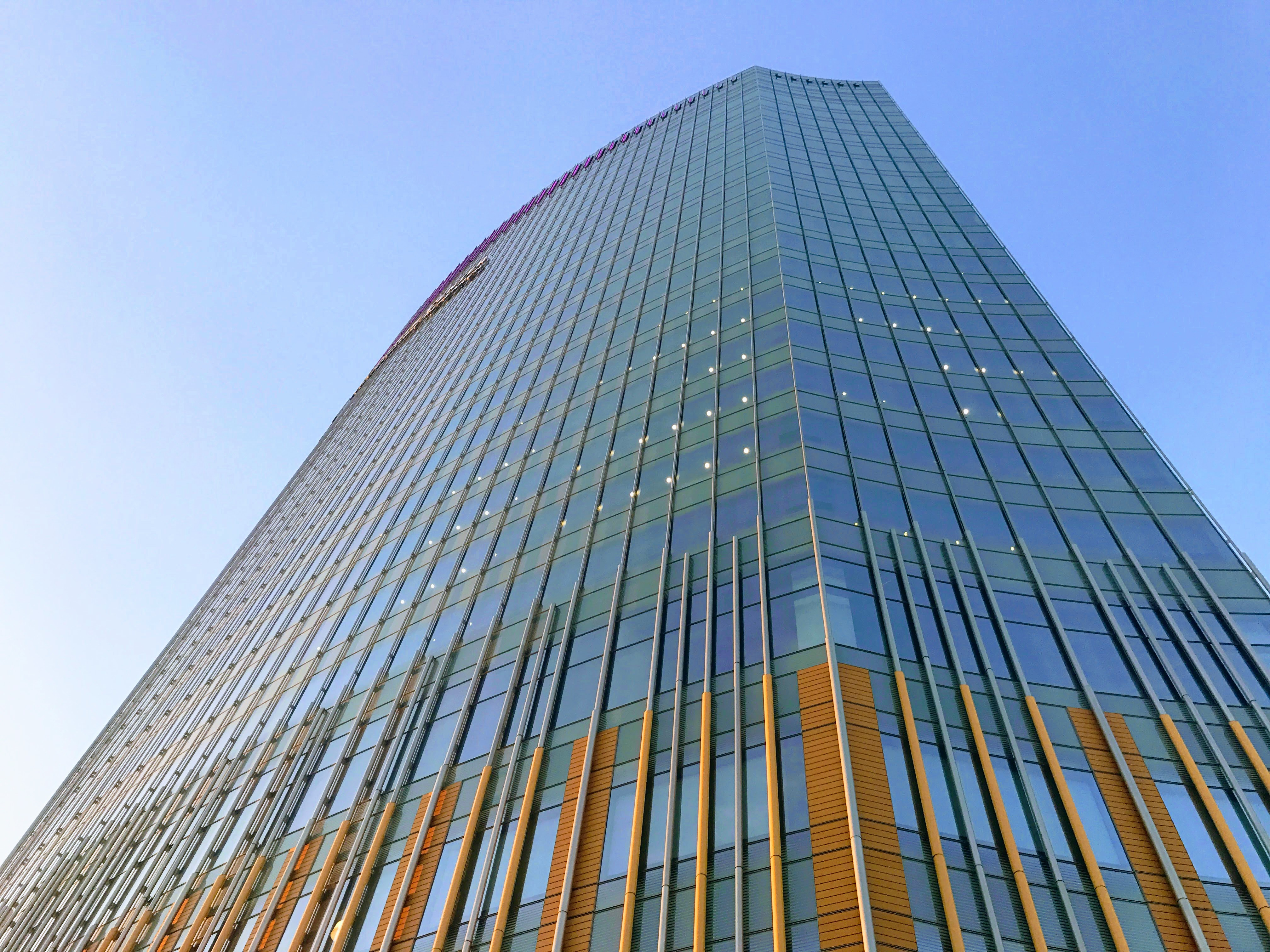 The exterior of the CHOP Tower in Philadelphia. The facade is glass with red structural details.