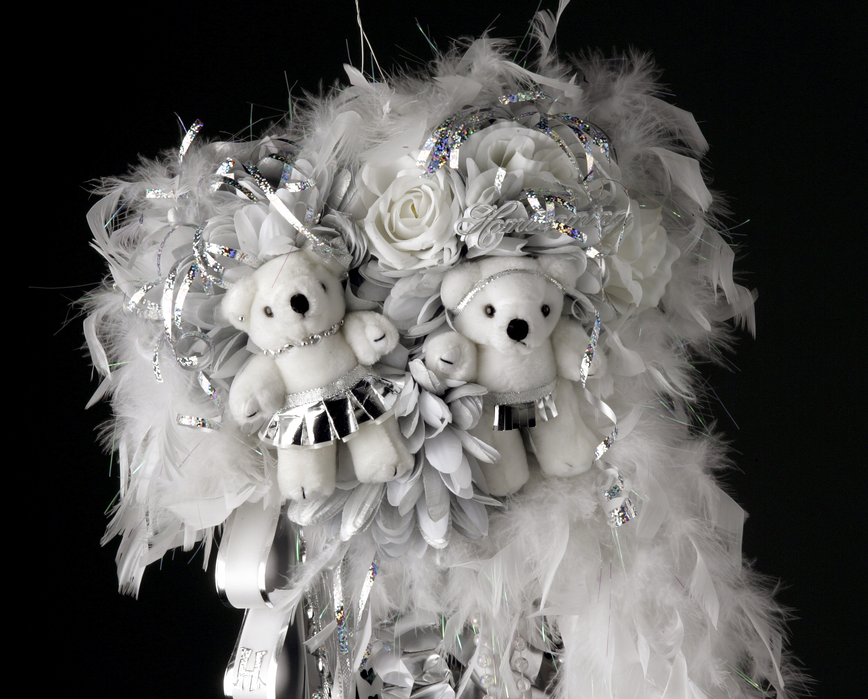 A silver and white homecoming mum with stuffed bears on it.