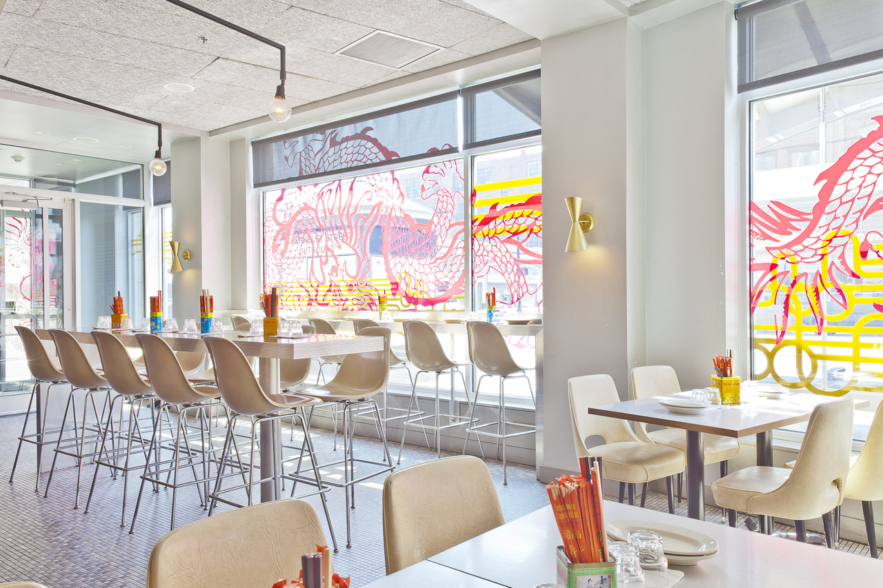 A brightly lit restaurant interior with a high-top table and some standard tables, all with white chairs. The sun-lit window is decorated by a large red and yellow dragon.