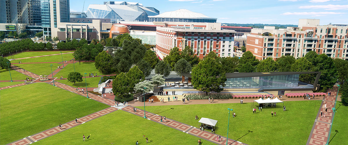 A glassy modern events facility across a grassy field.