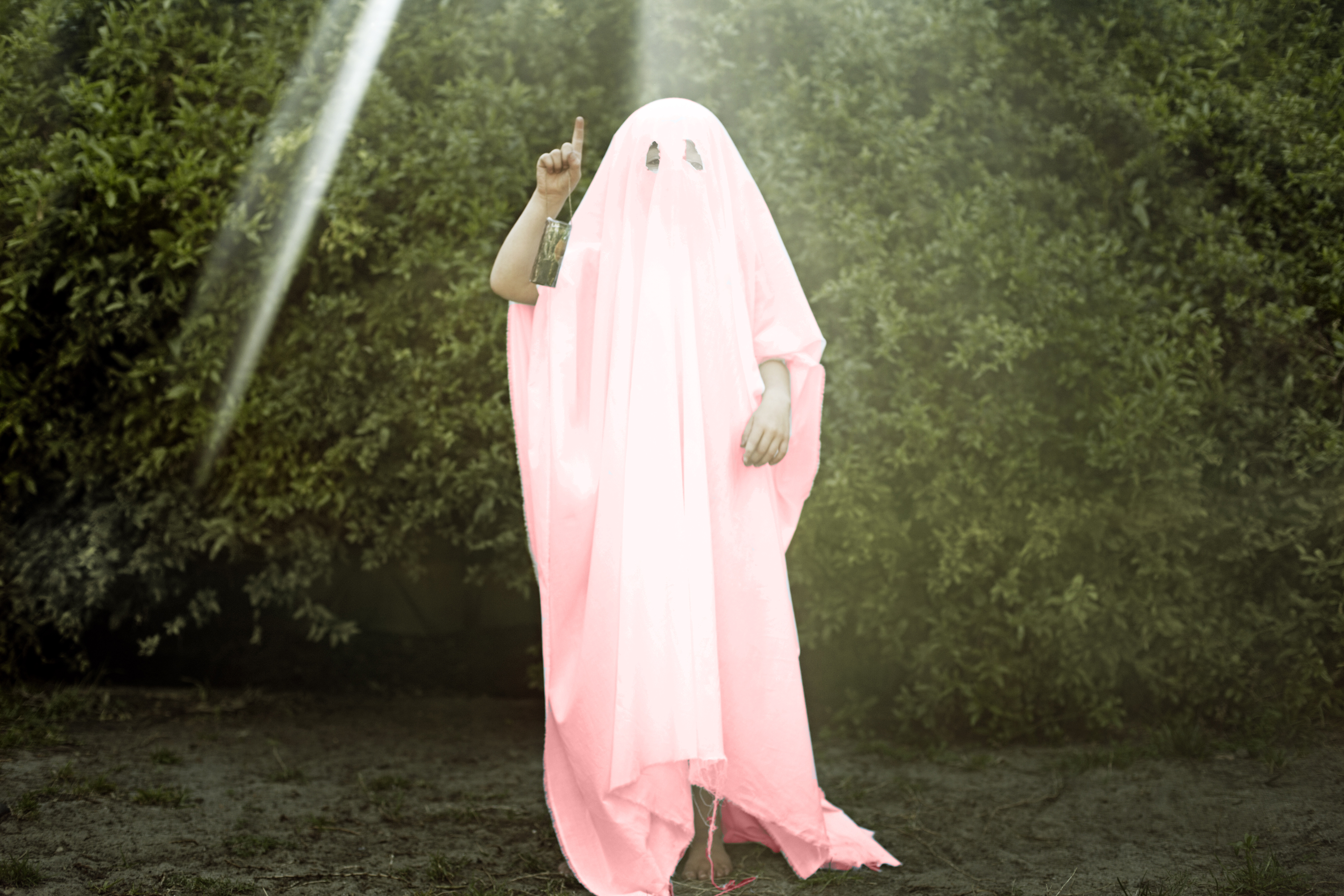 A person covered in a pink sheet as the ghost of millennial pink.
