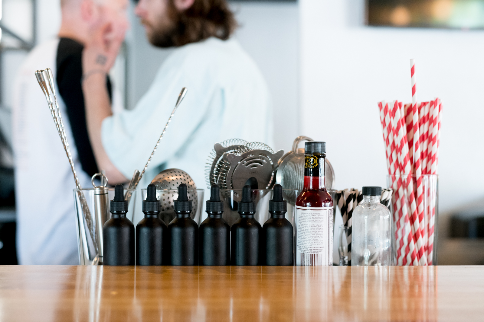 A bar set with bitters, strainers, and a glass cup of paper straws