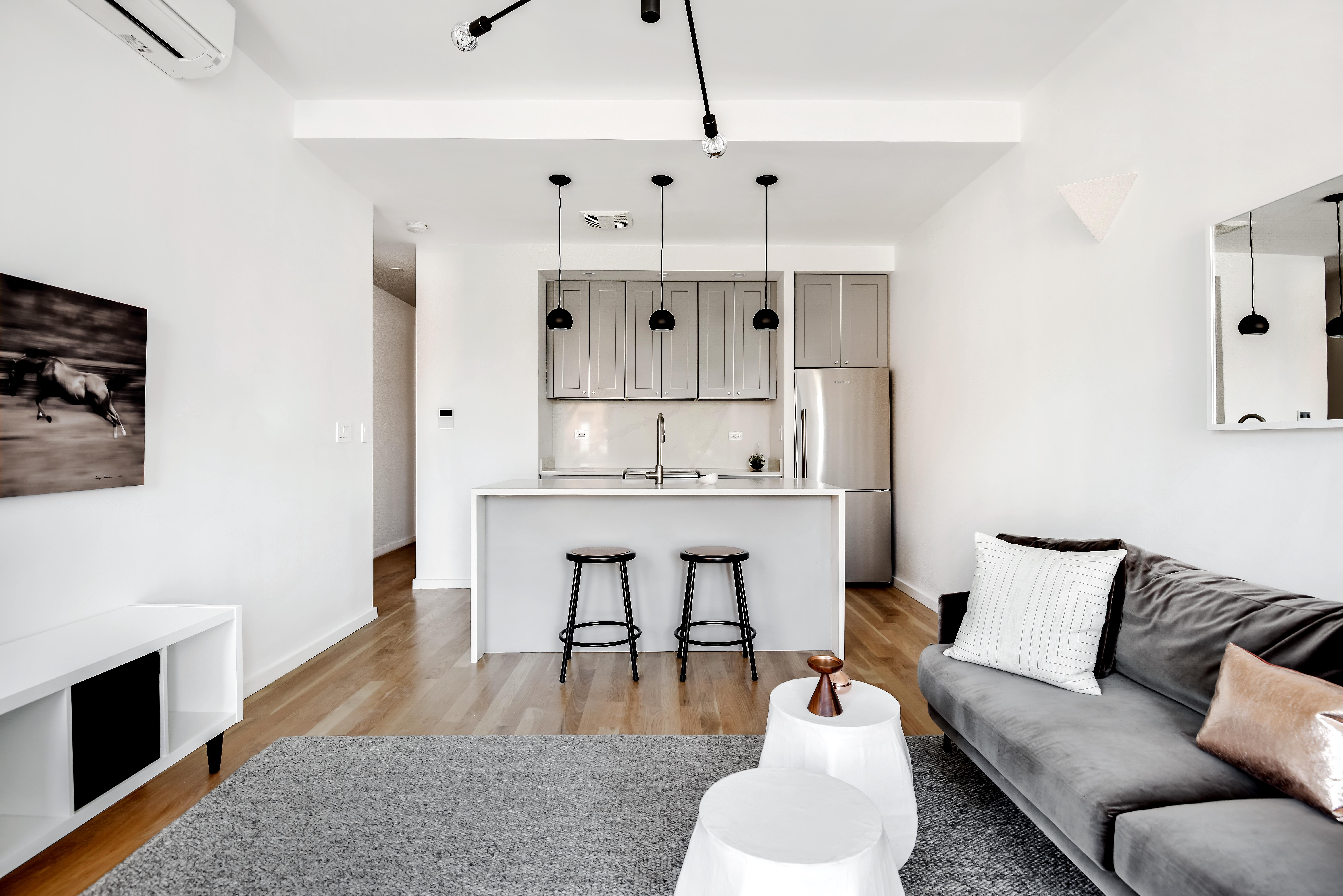 View of small apartment kitchen from white-walled minimalist living room.