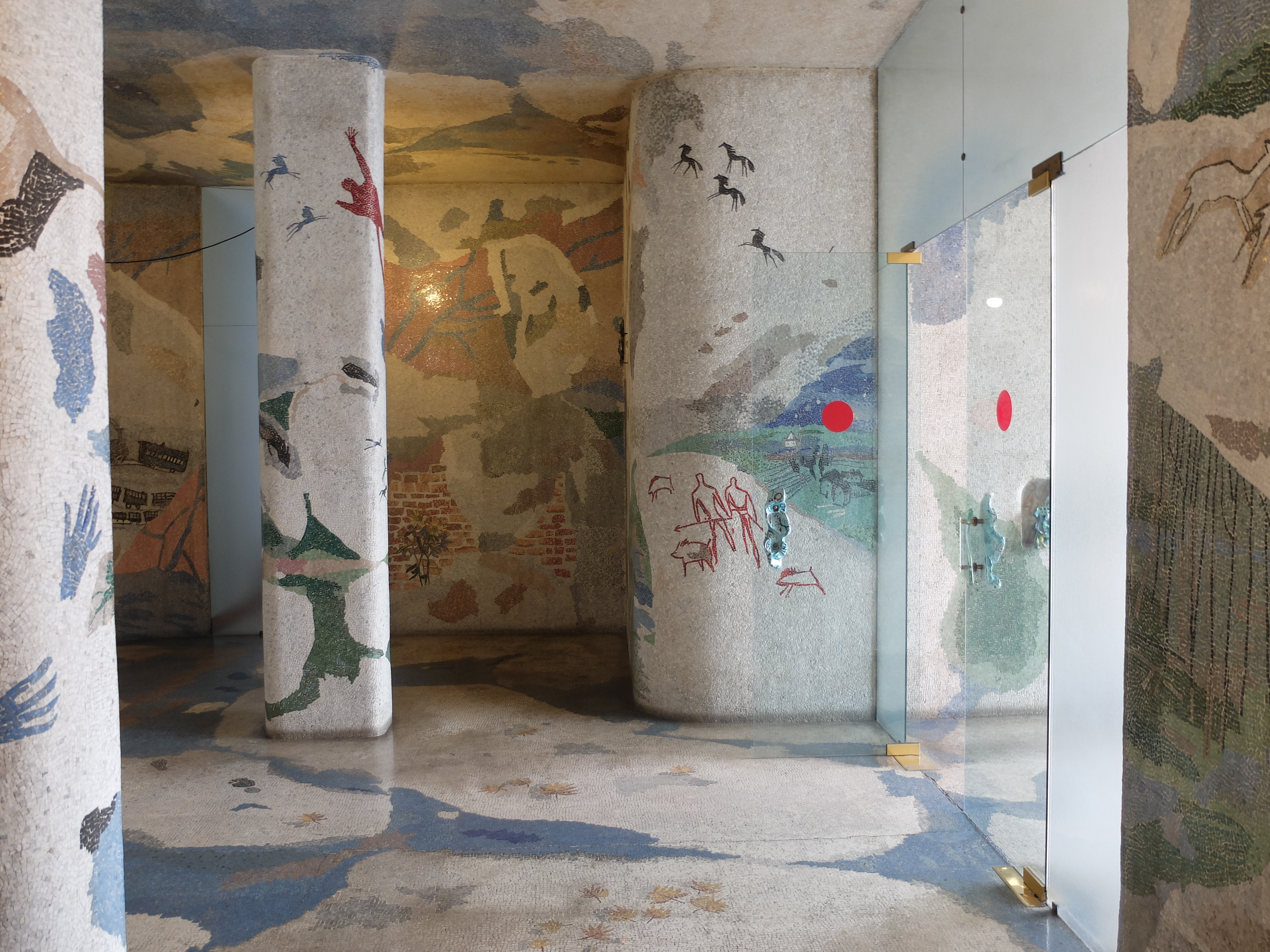 Photo of a lobby foyer with walls, columns, floors, and ceilings mosaiced with abstract shapes and hand prints and animals.