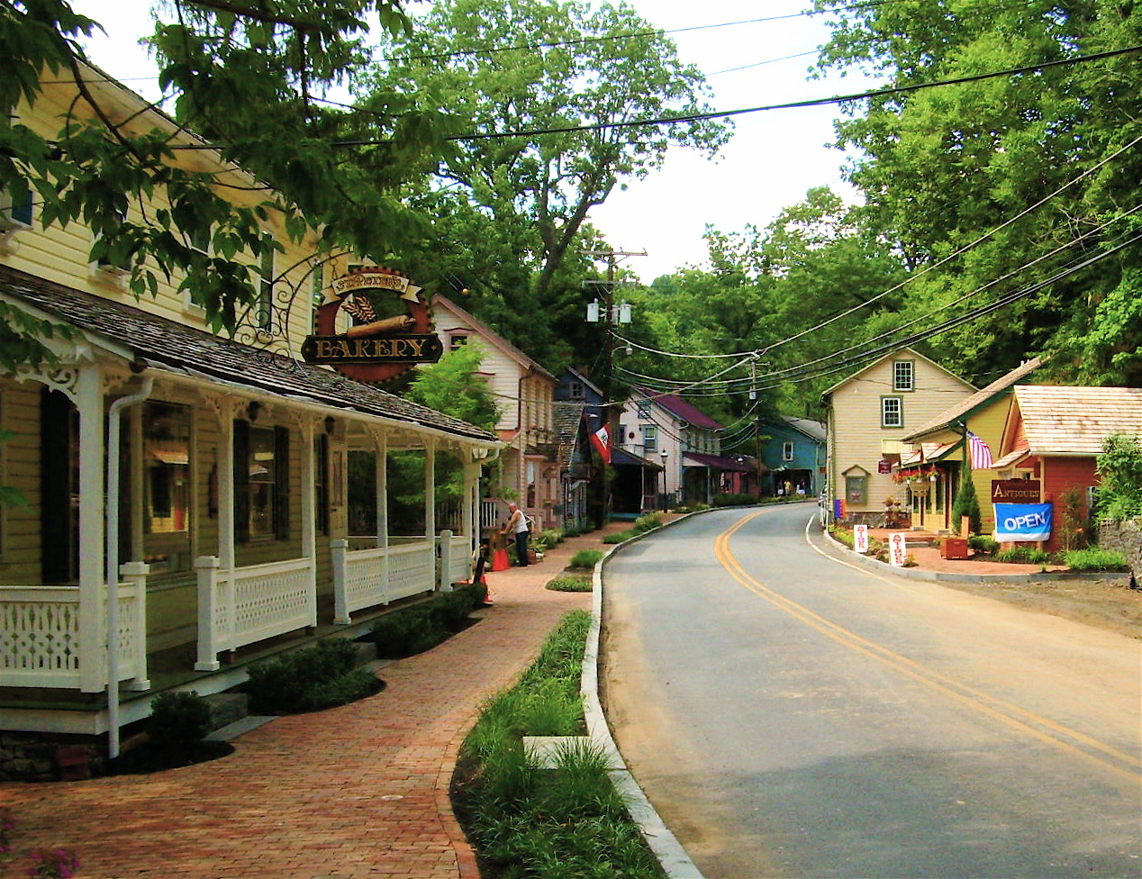 A street running through a small town near Philadelphia. The street is lined with houses and shops. The house in the foreground has a porch with a white fence. There are trees in the background.