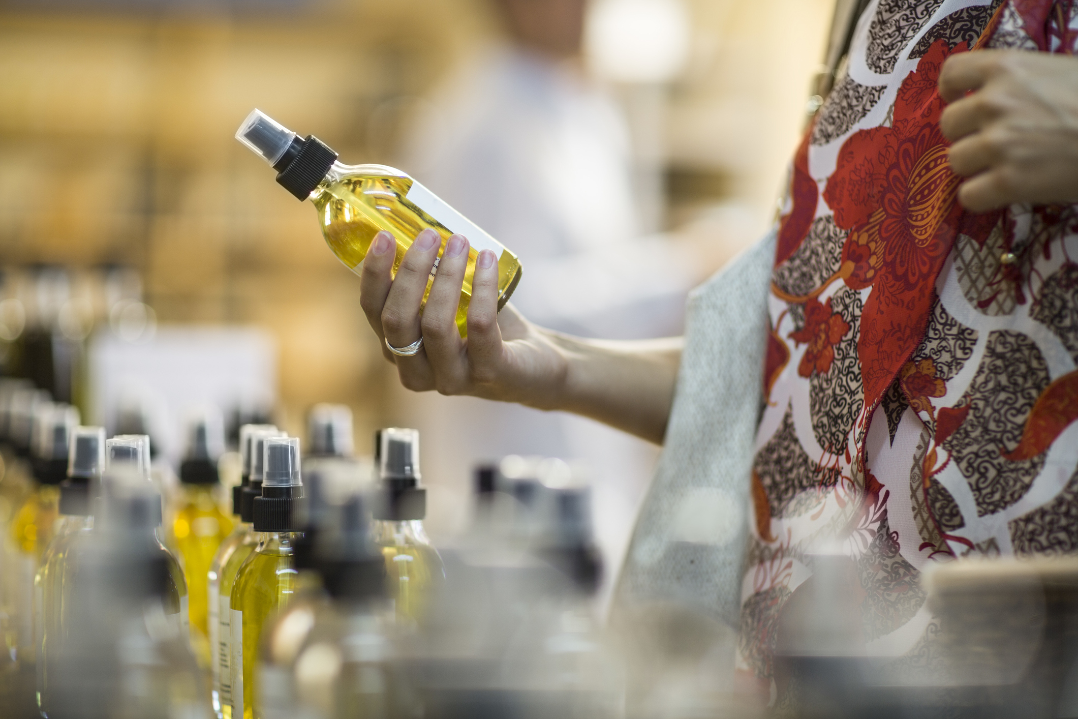 A woman holding a bottle of perfume in a store