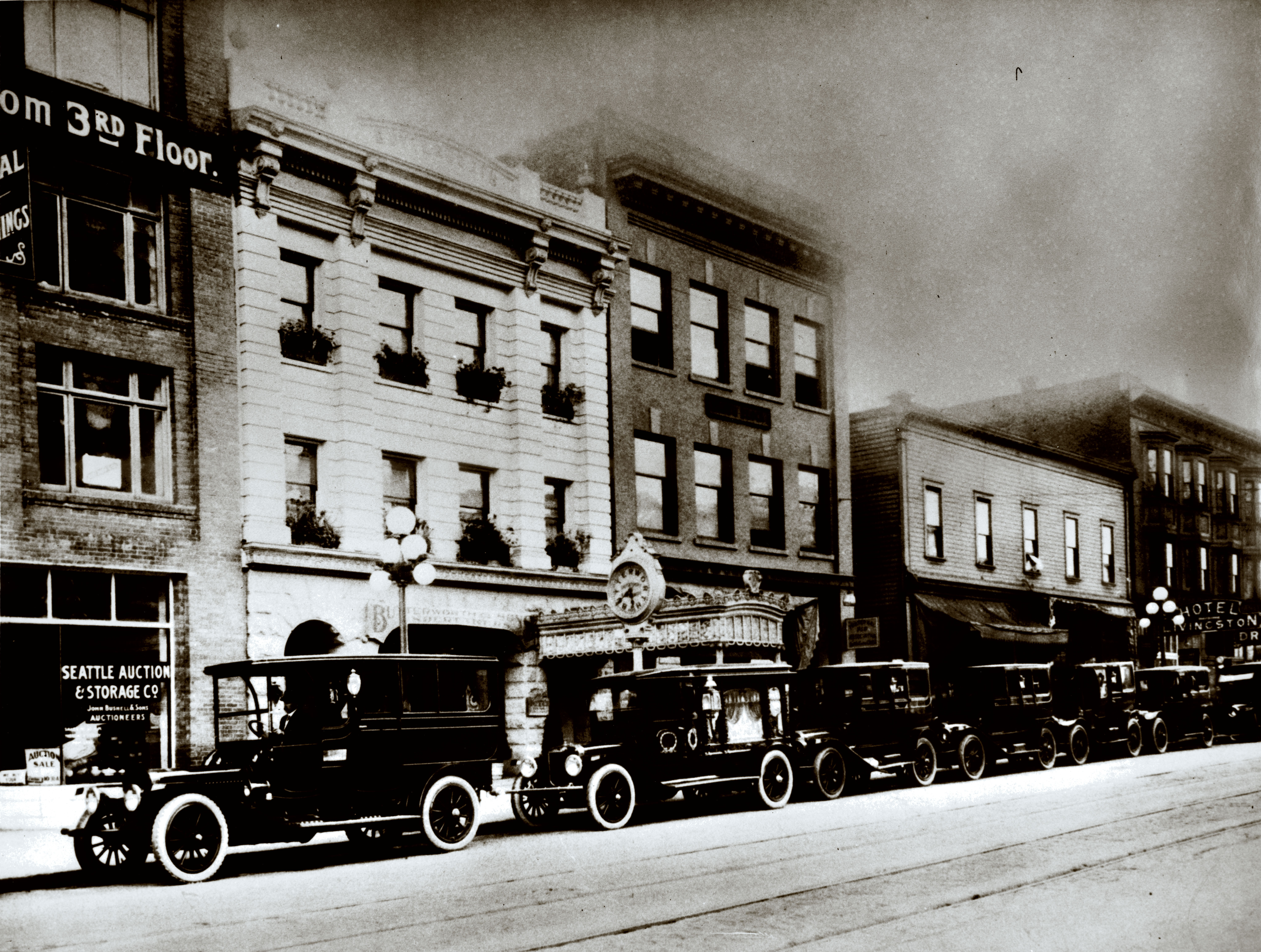 A row of black cars is in front of a row of houses in Seattle. This is an old black and white photograph.