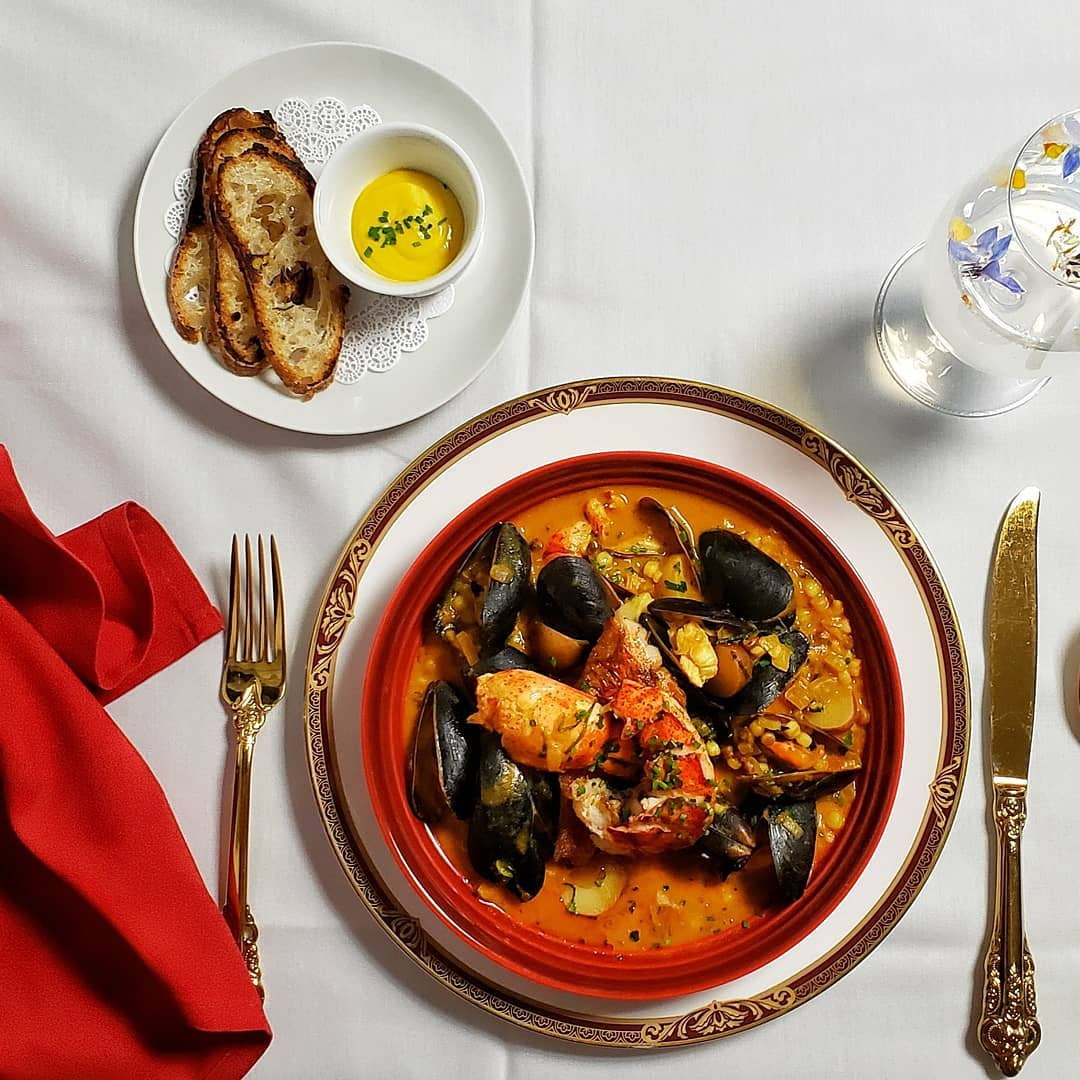 gold-rimmed plate with seafood stew