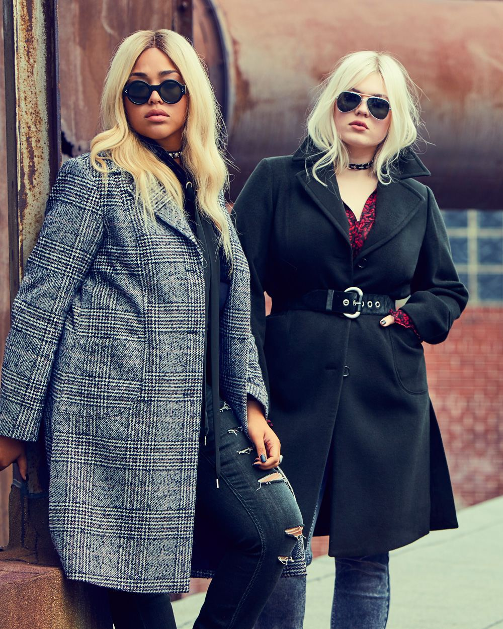 Two models in sunglasses and coats