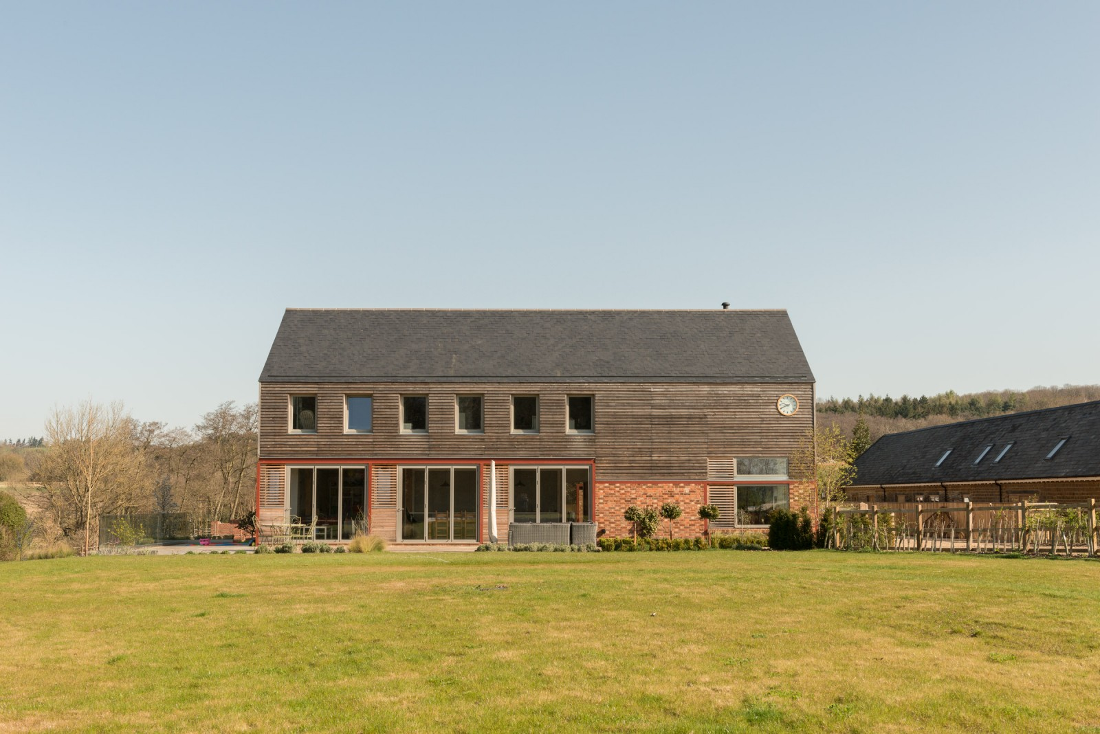 Modern farmhouse with timber-clad second floor and brick-clad main floor on two acres of land.